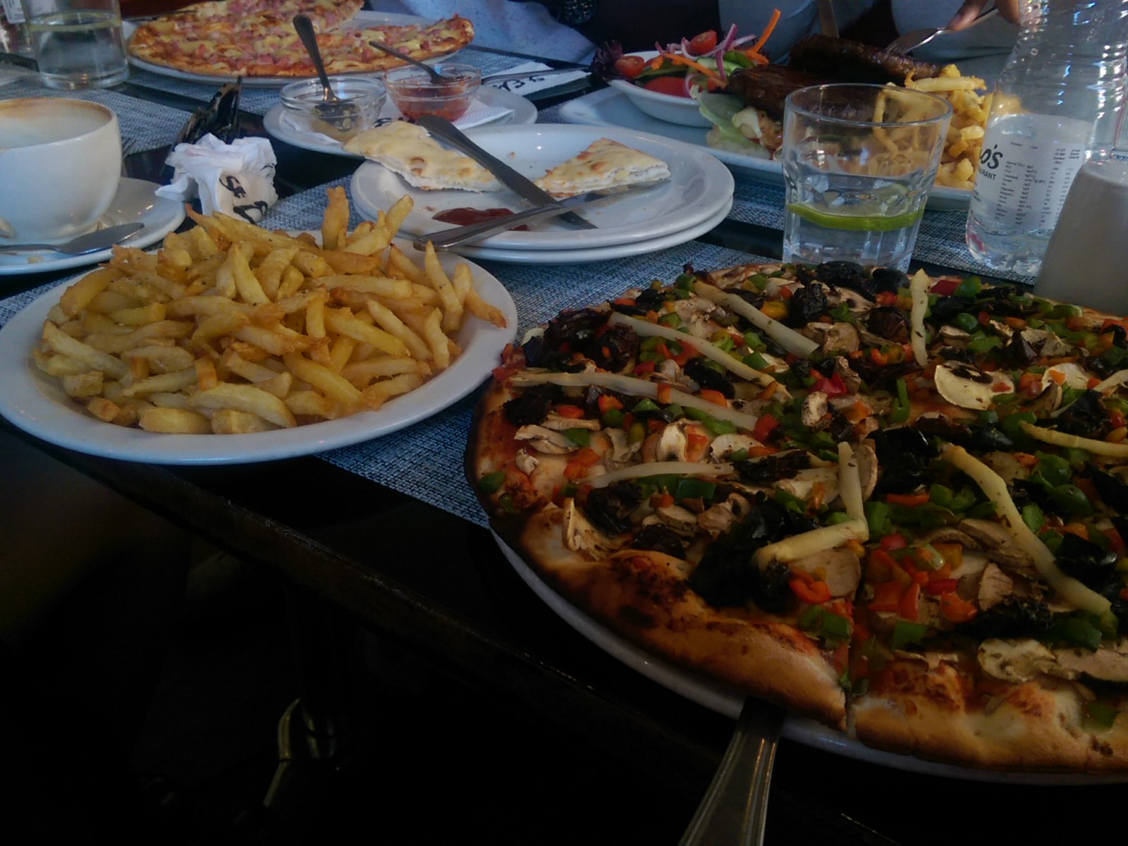 A table full of food, closest a pizza with vegetables beside a large plate of fries