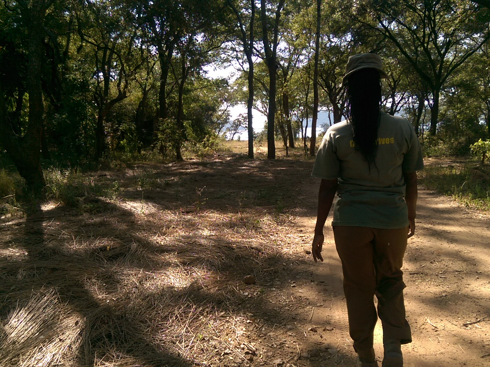 A black woman with dreads and a green hat walking along a dirt road surrounded by trees, from behind