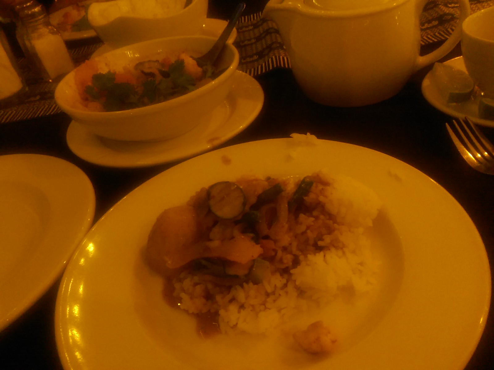 A white plate with a pile of rice and vegetable curry, and a bowl of curry beside it