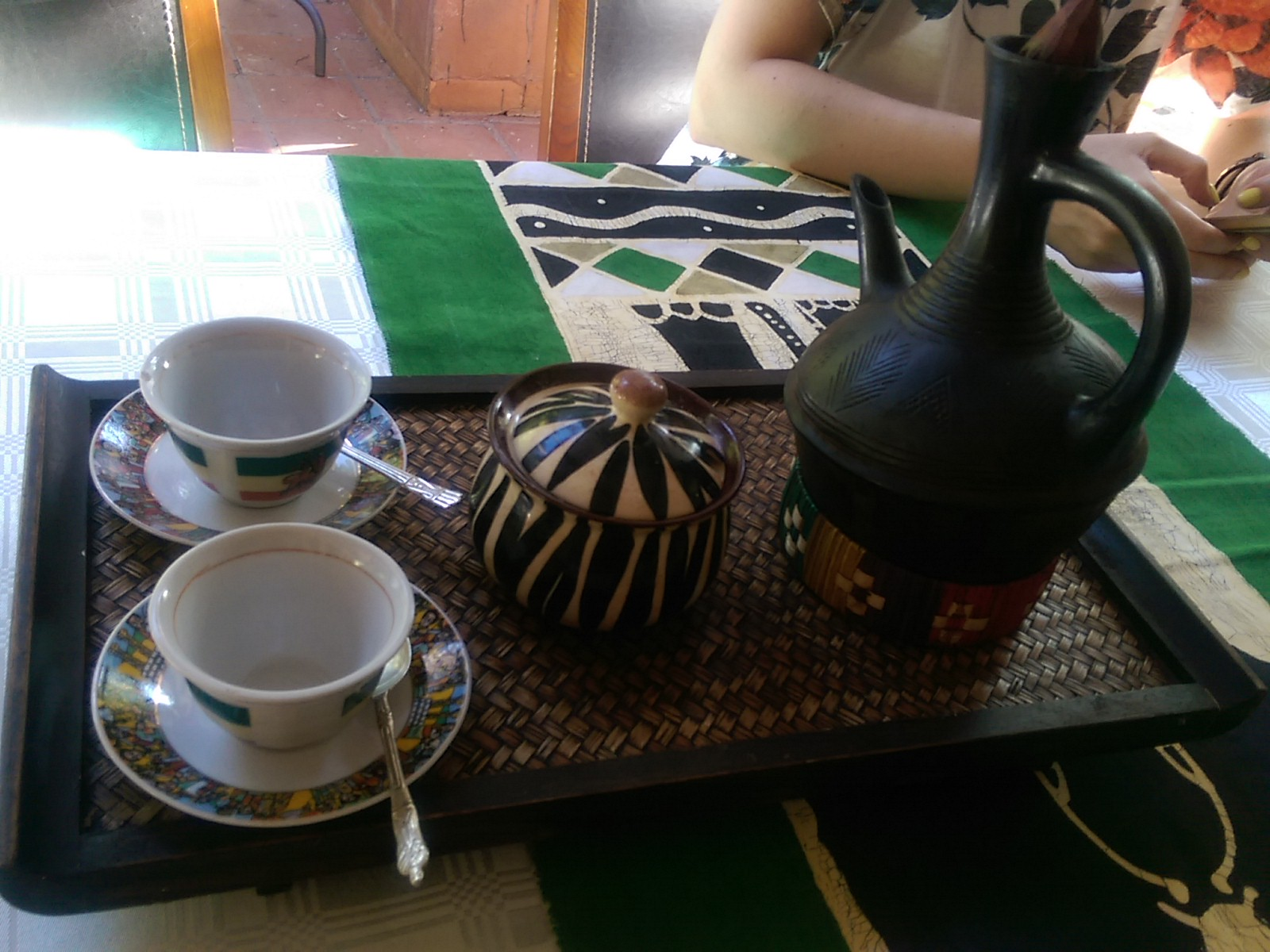 A tray with two small white cups, a stripey patterned sugar pot and a black spouted coffee pot