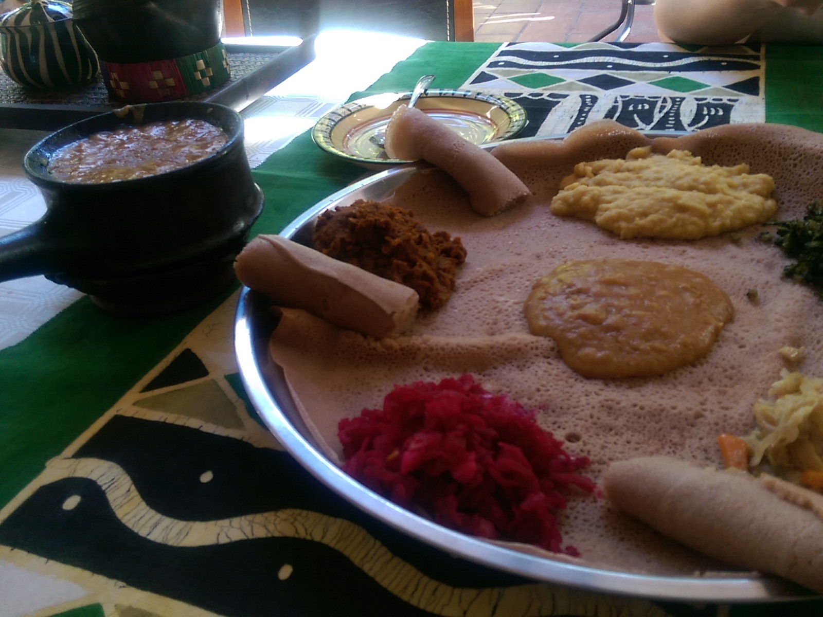 A metal plate with flat and rolled injera and splodges of coloured vegetable curries