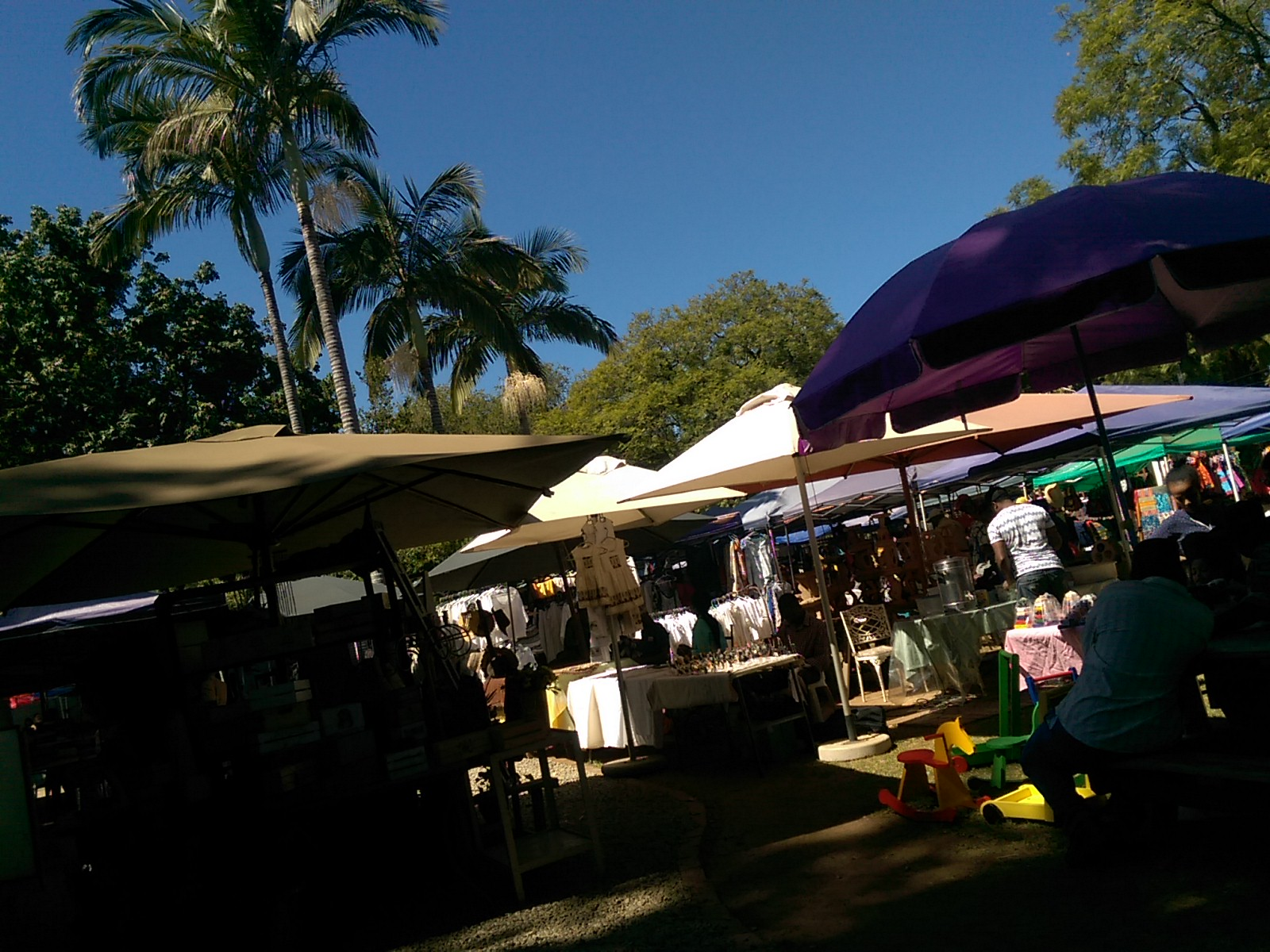 Colourful awnings at a market full of people, with a bright blue sky and palm trees