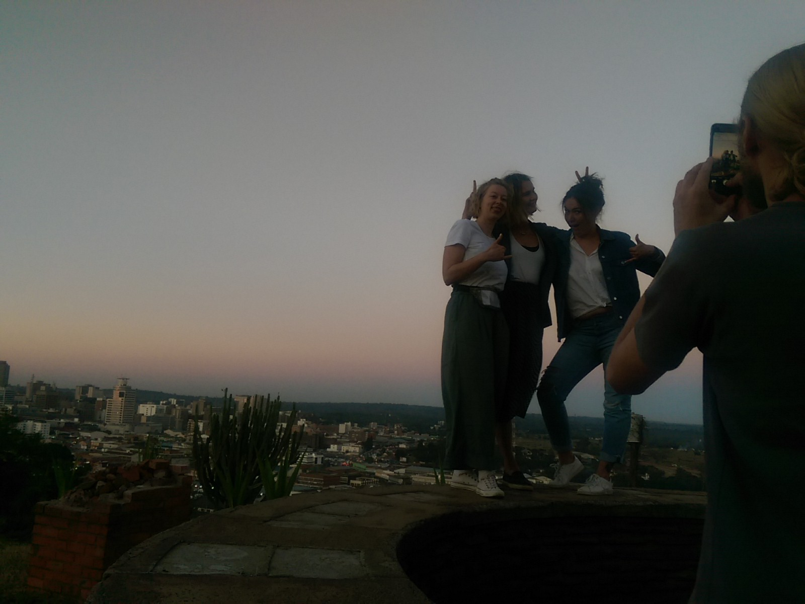 Three women pose on a wall with a dusk cityscape in the background while a man in the foreground takes a photo