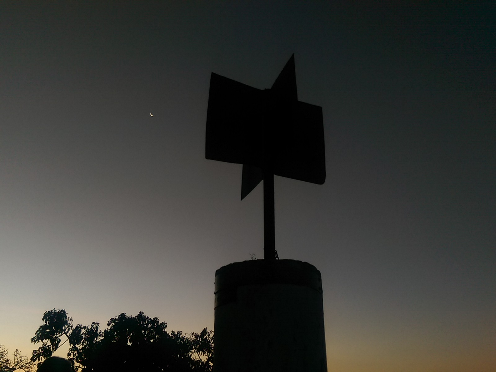 A 4-way sign post silhouetted against a post-sunset sky with the moon beside it