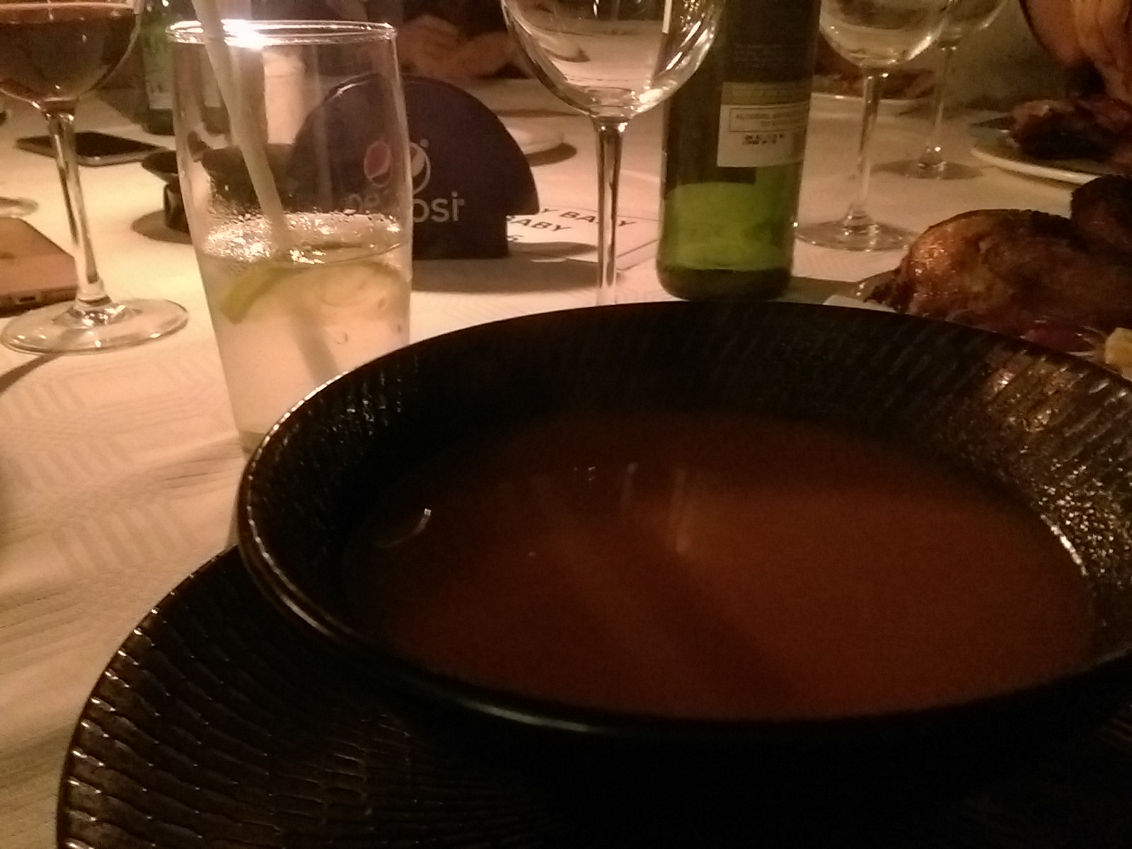 A dark bowl with red soup on a table with wine glasses in the background