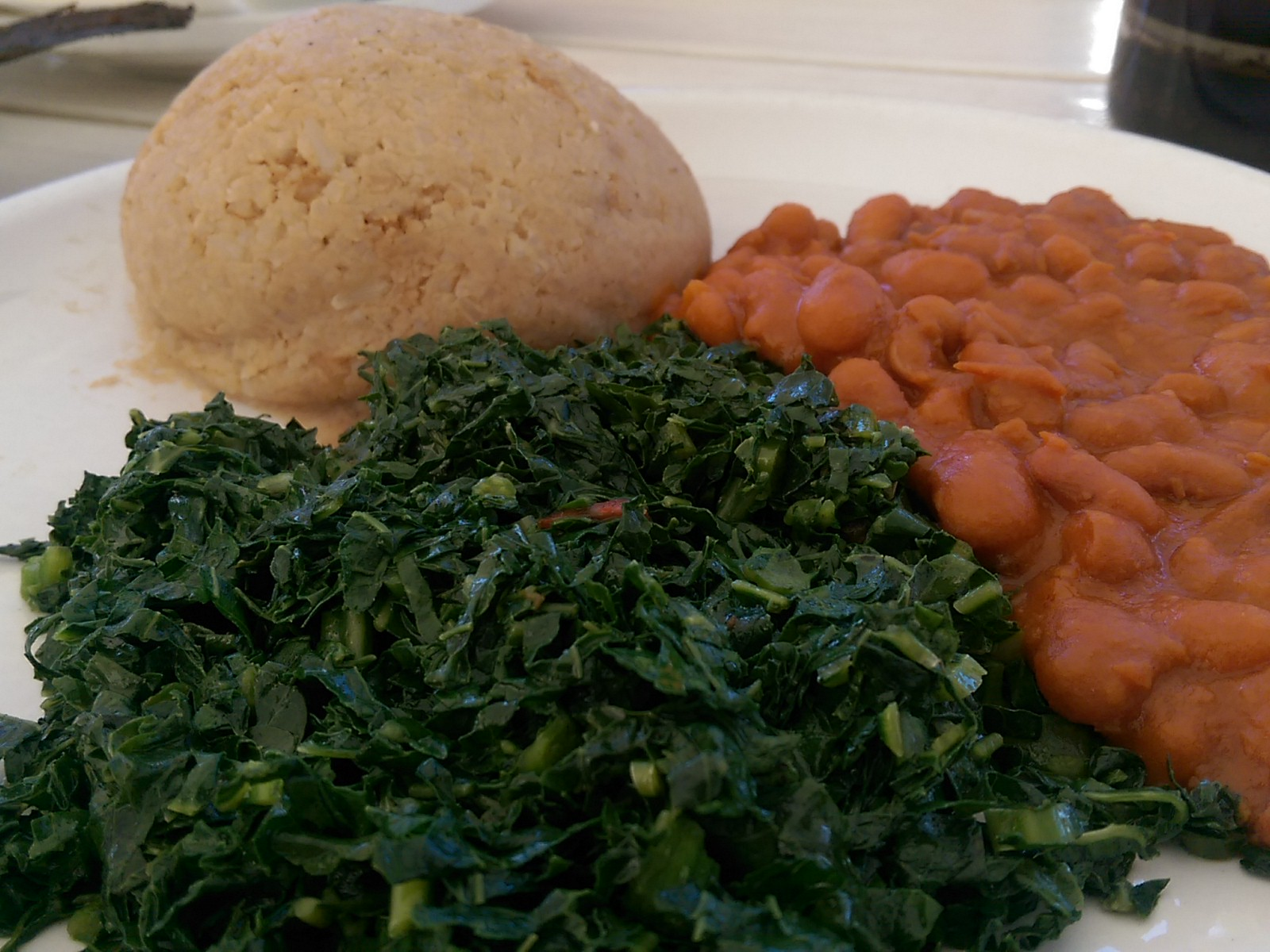 A white plate with a close up of greens and beans with a round ball of peanut rice in the background