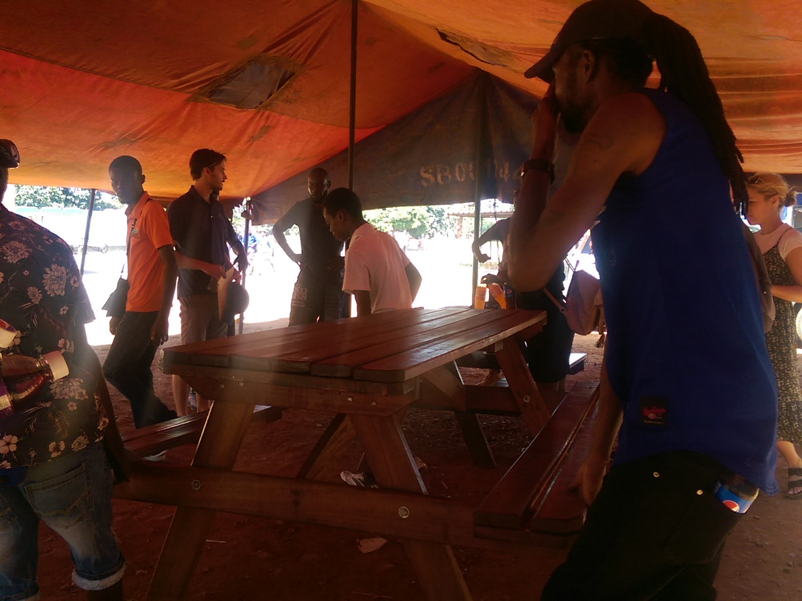 Several people are moving a bench under an orange awning