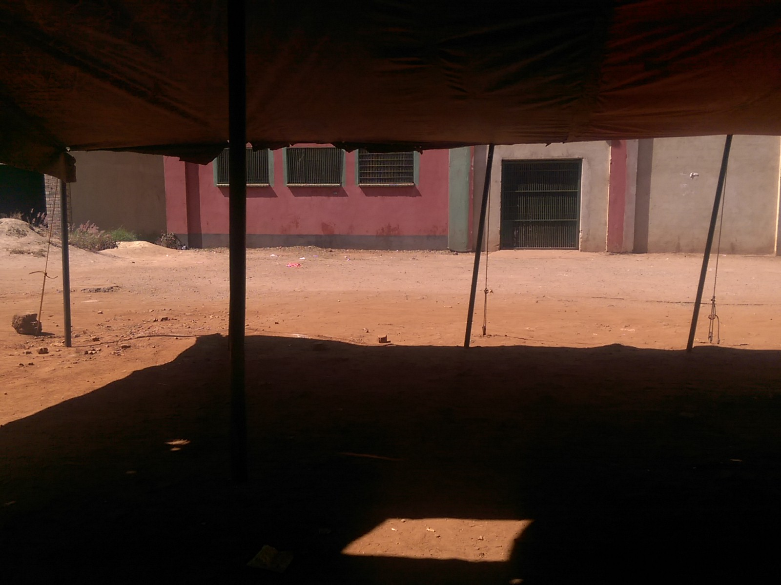 Under an orange-tinged awning that casts shadow on the sandy ground
