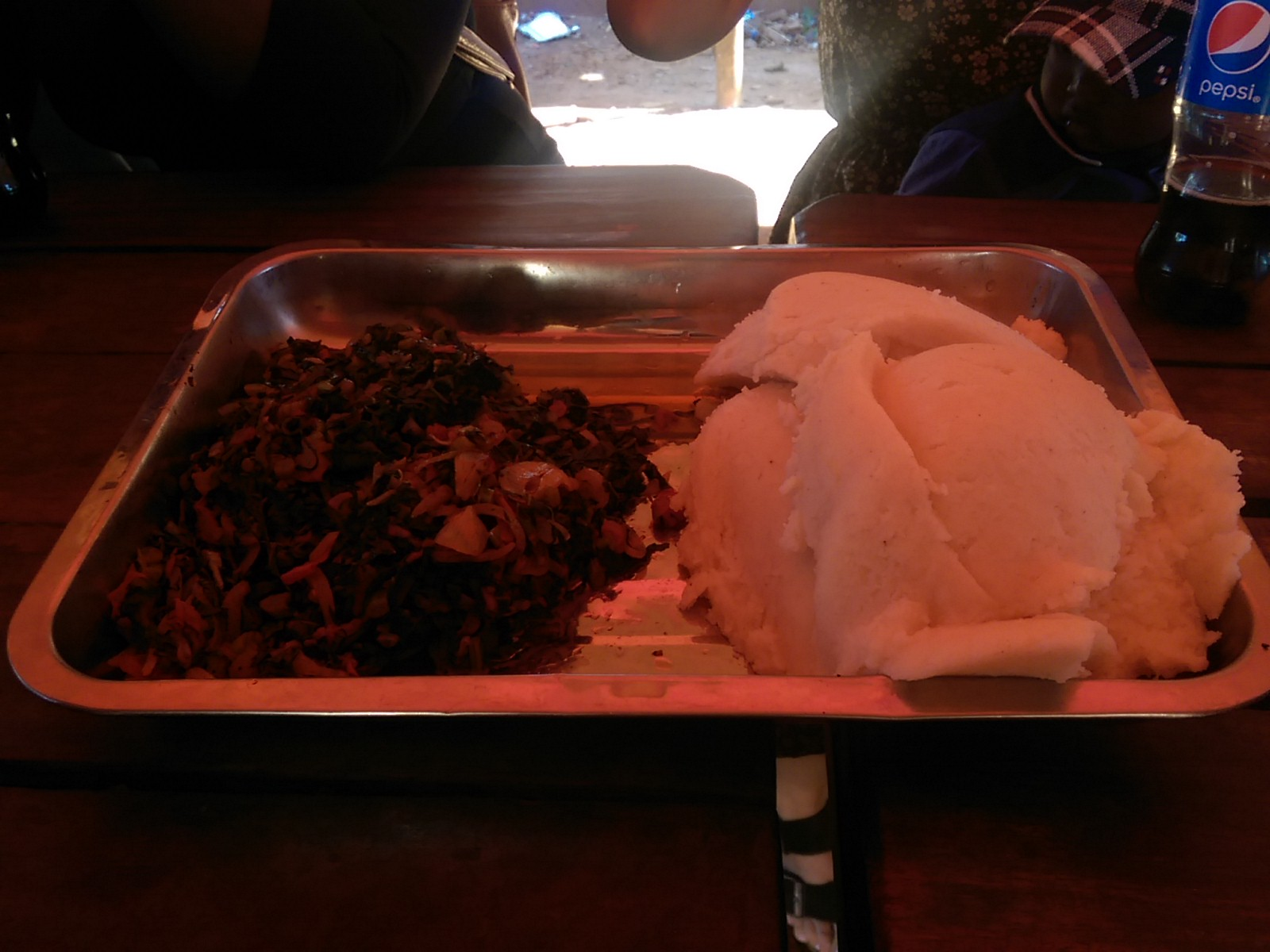 A rectangular metal tray with a huge pile of white sadza to the right of greens