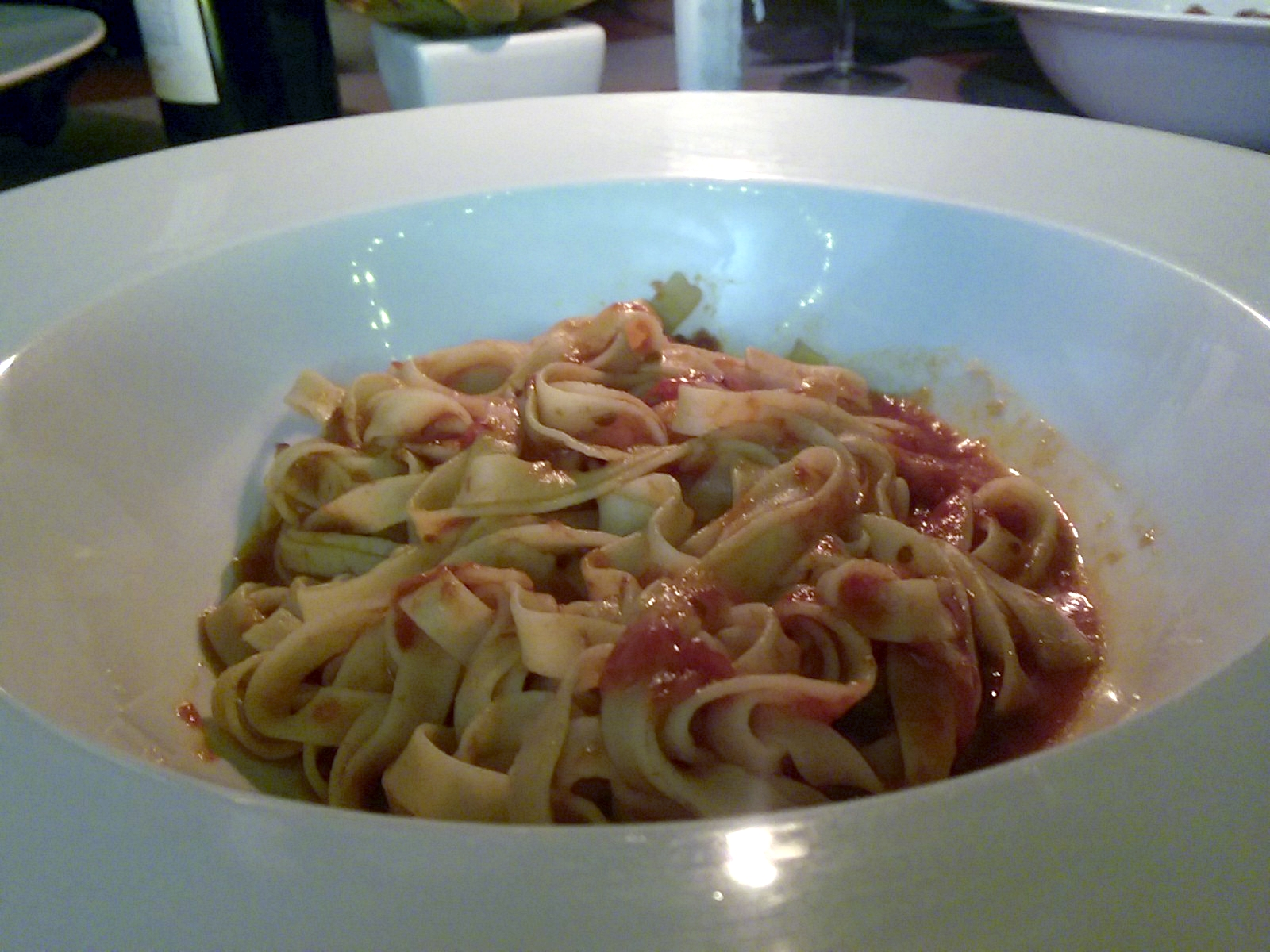 A white bowl with wide pasta and tomato sauce