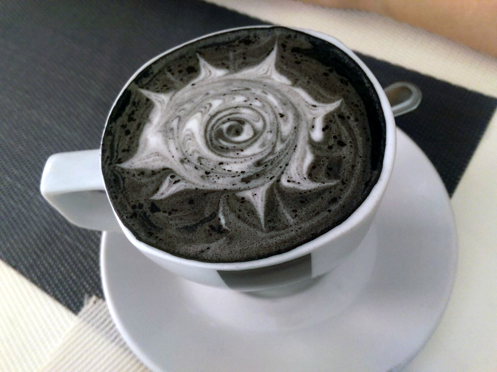 A white cup with a black beverage and latte art