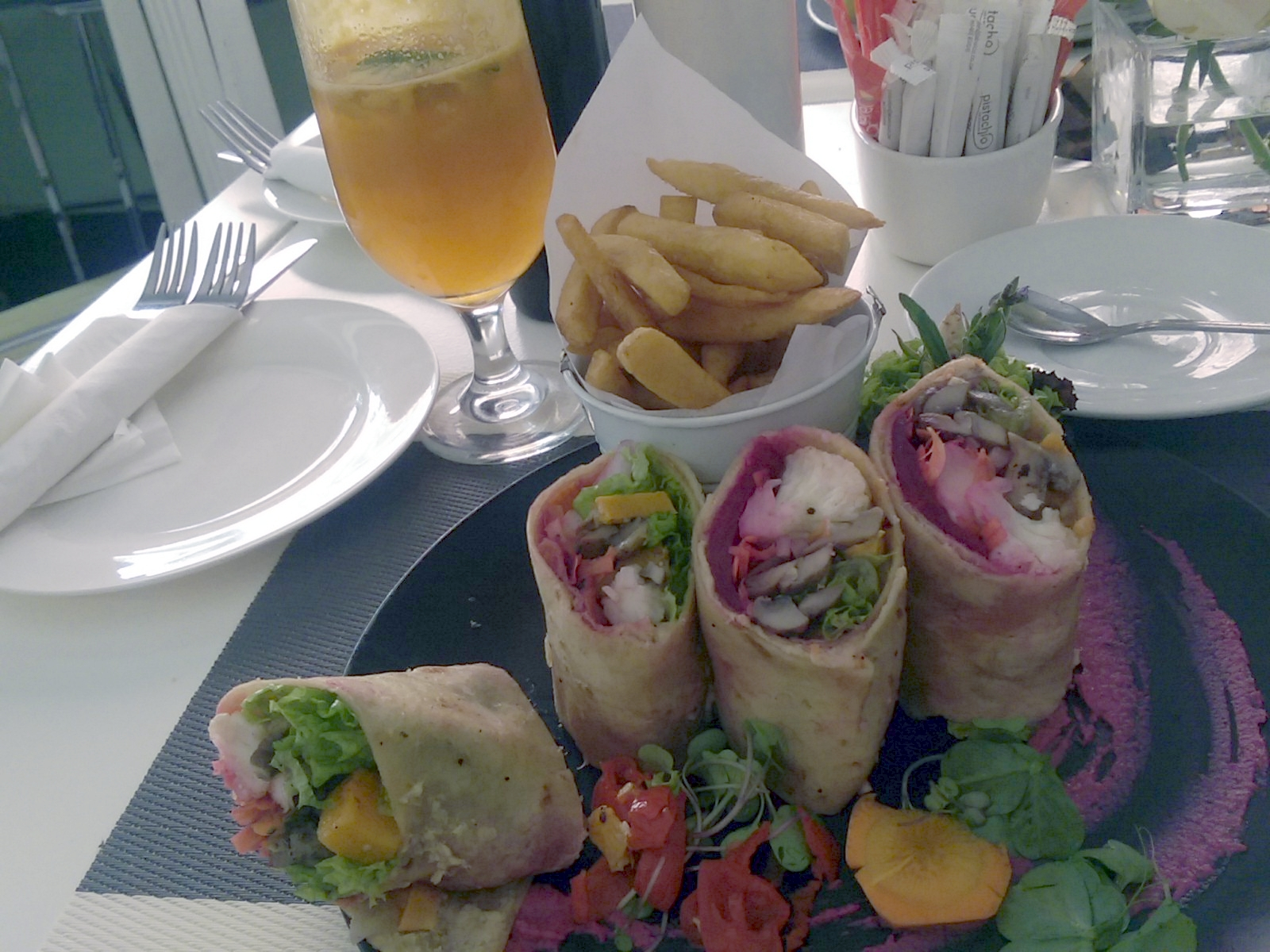 A plate with four small vegetable wraps, three on end, one fallen over, with a bowl of chips and a glass of apple juice behind them