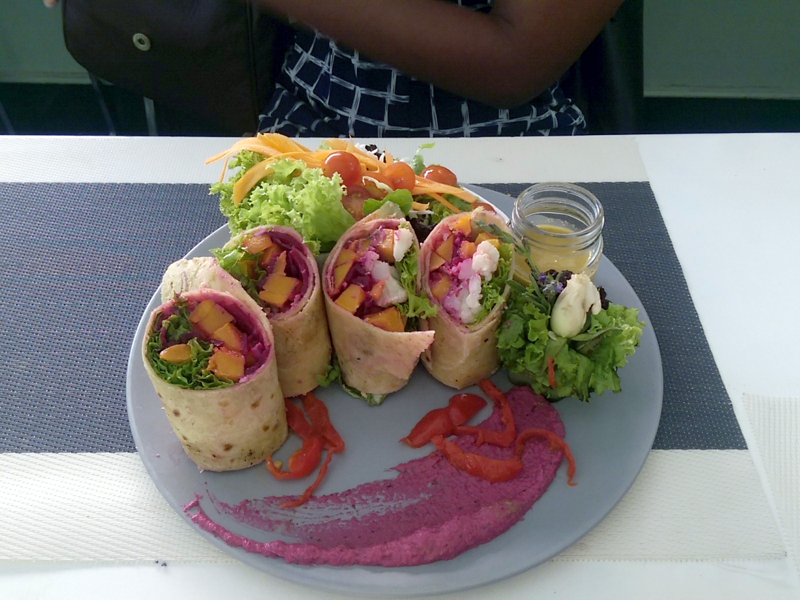 Four small tortillas standing on end filled with vegetables on a plate with salad