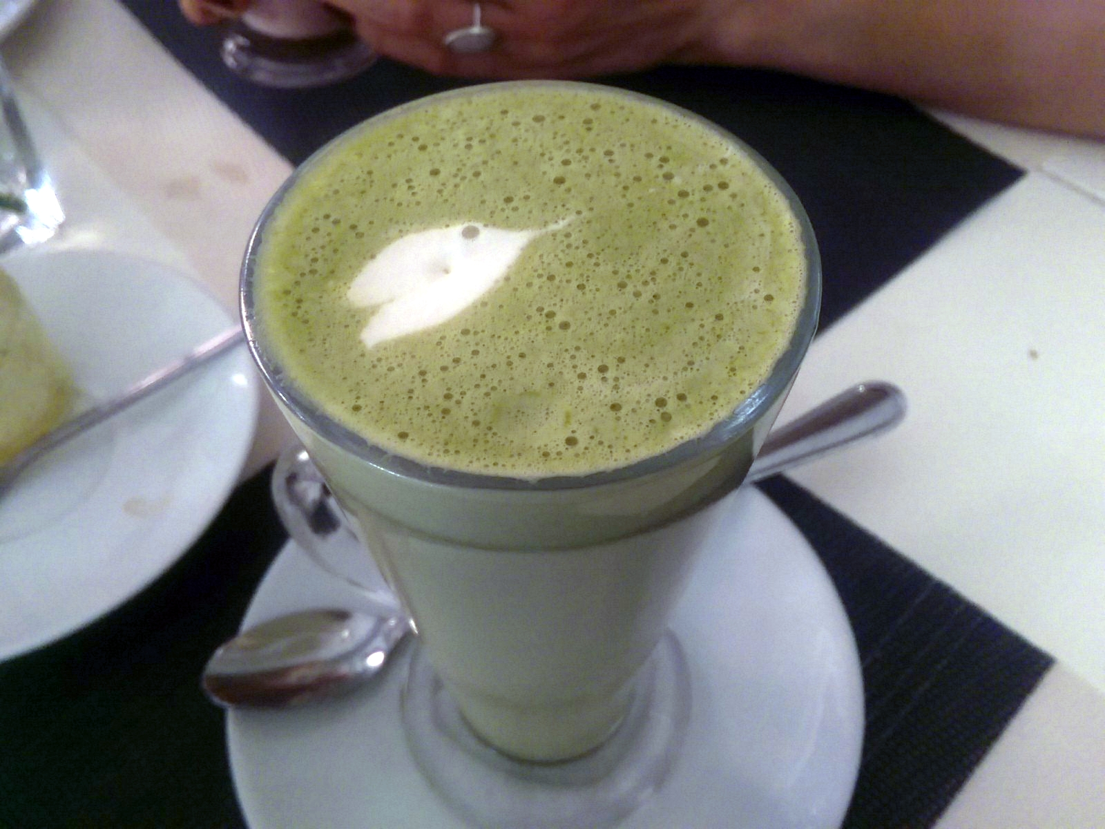 A tall glass with green foamy drink
