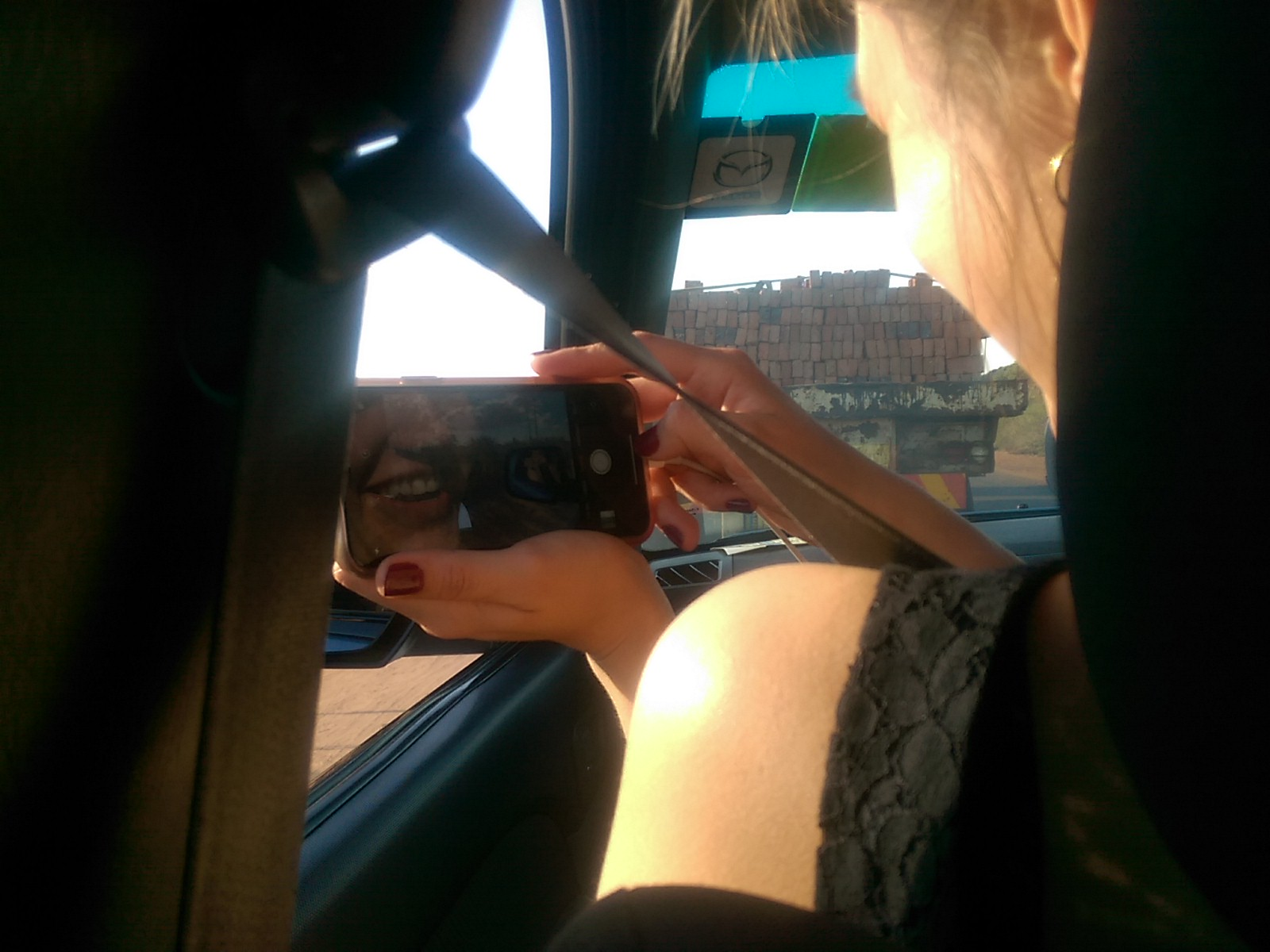 From behind the front seat, a woman takes a photo out of a car window