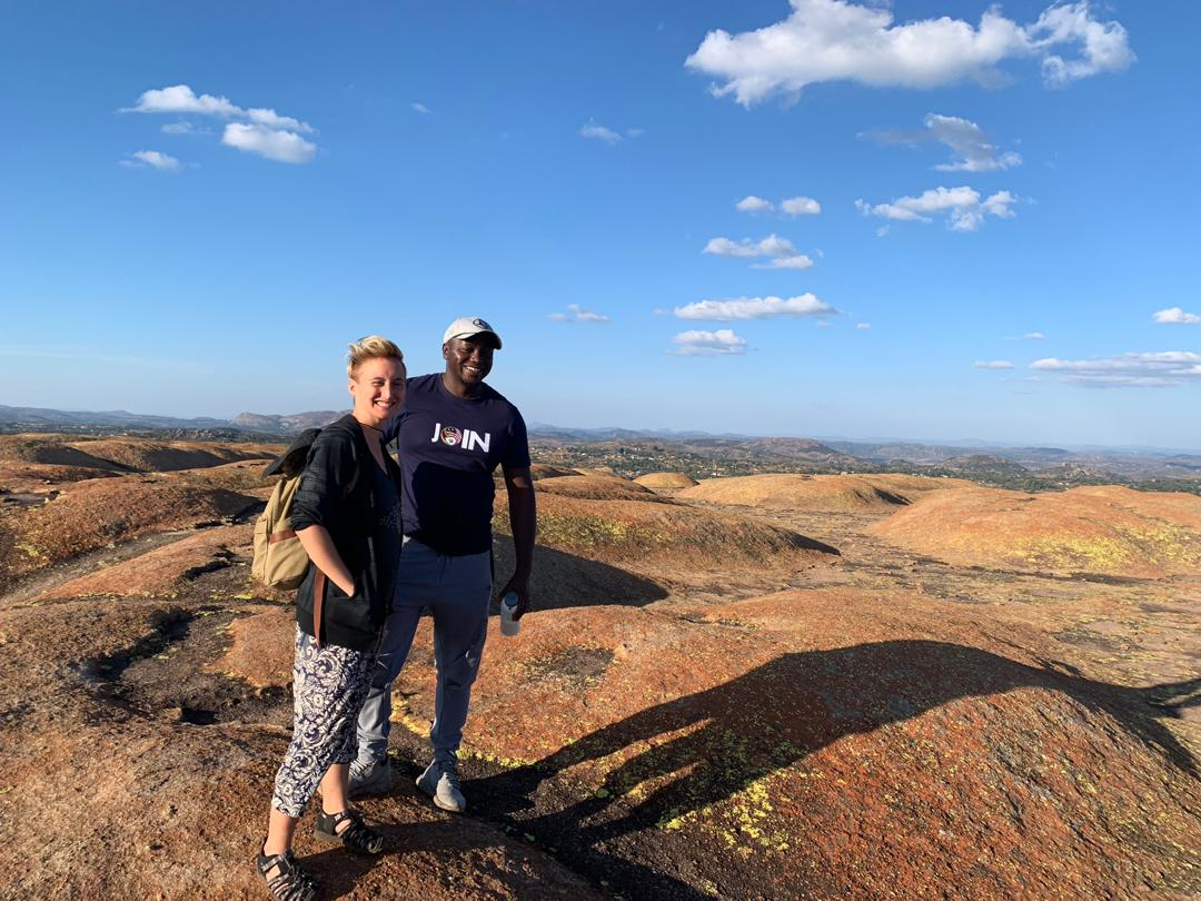 A woman and a man stand on a granite hill with blue sky and fluffy clouds