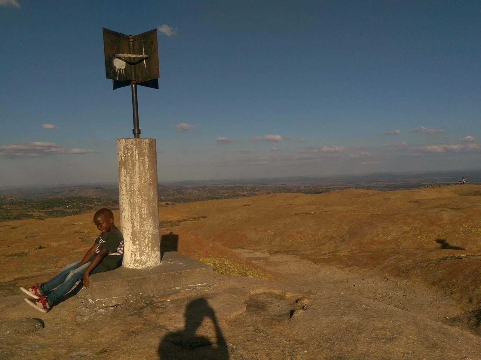 A child sits by a sign on top of a granite hill