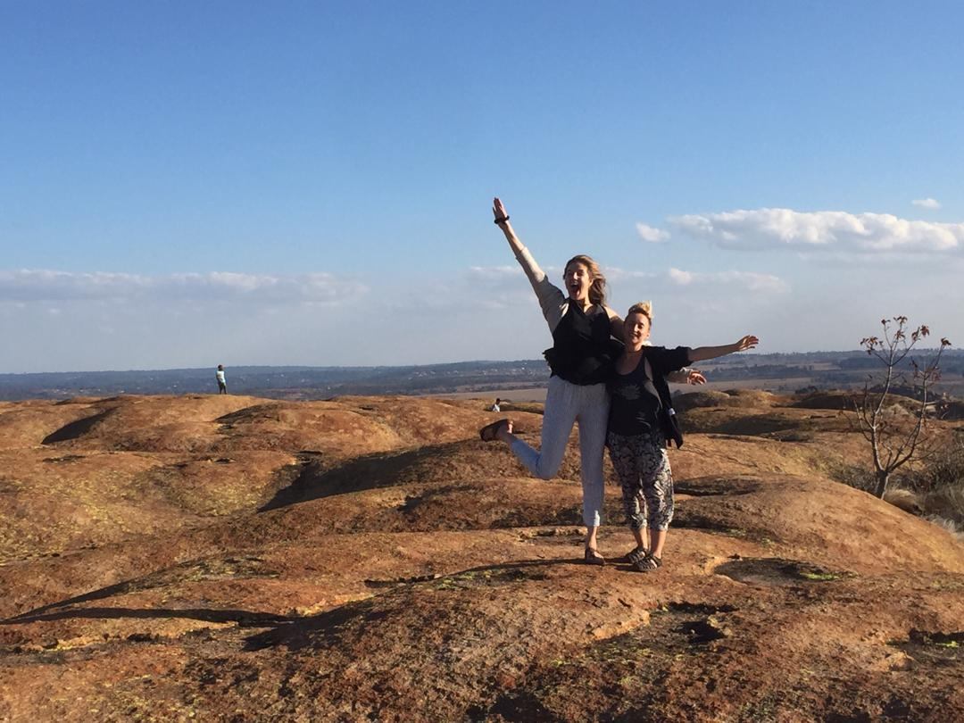Two women wave their arms on a granite hill wiht blue sky and fluffy clouds