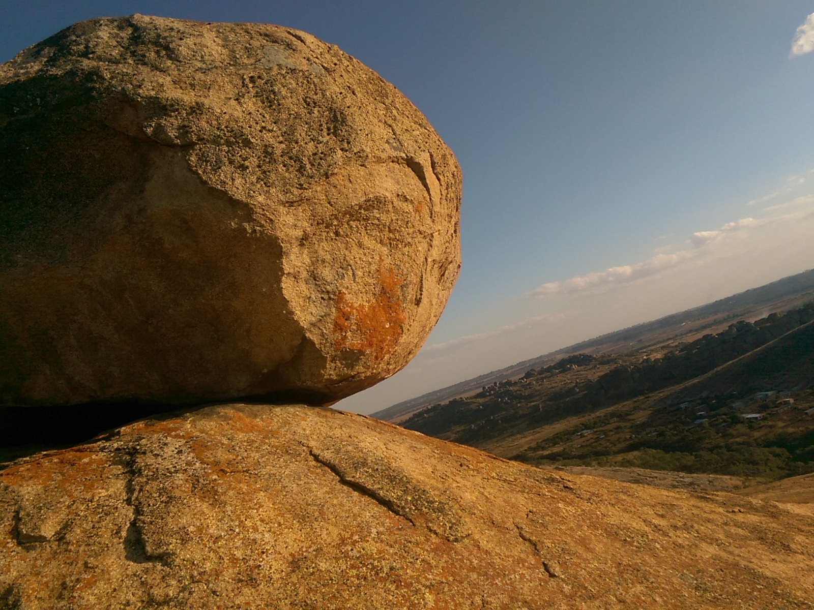 A large rock lit by the sun with a view across granite hills