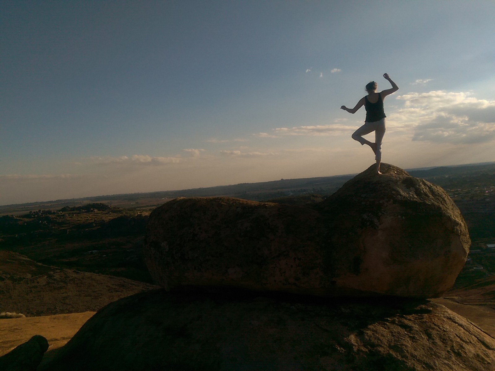 The silhouette of a woman balancing on a large rock with an epic view