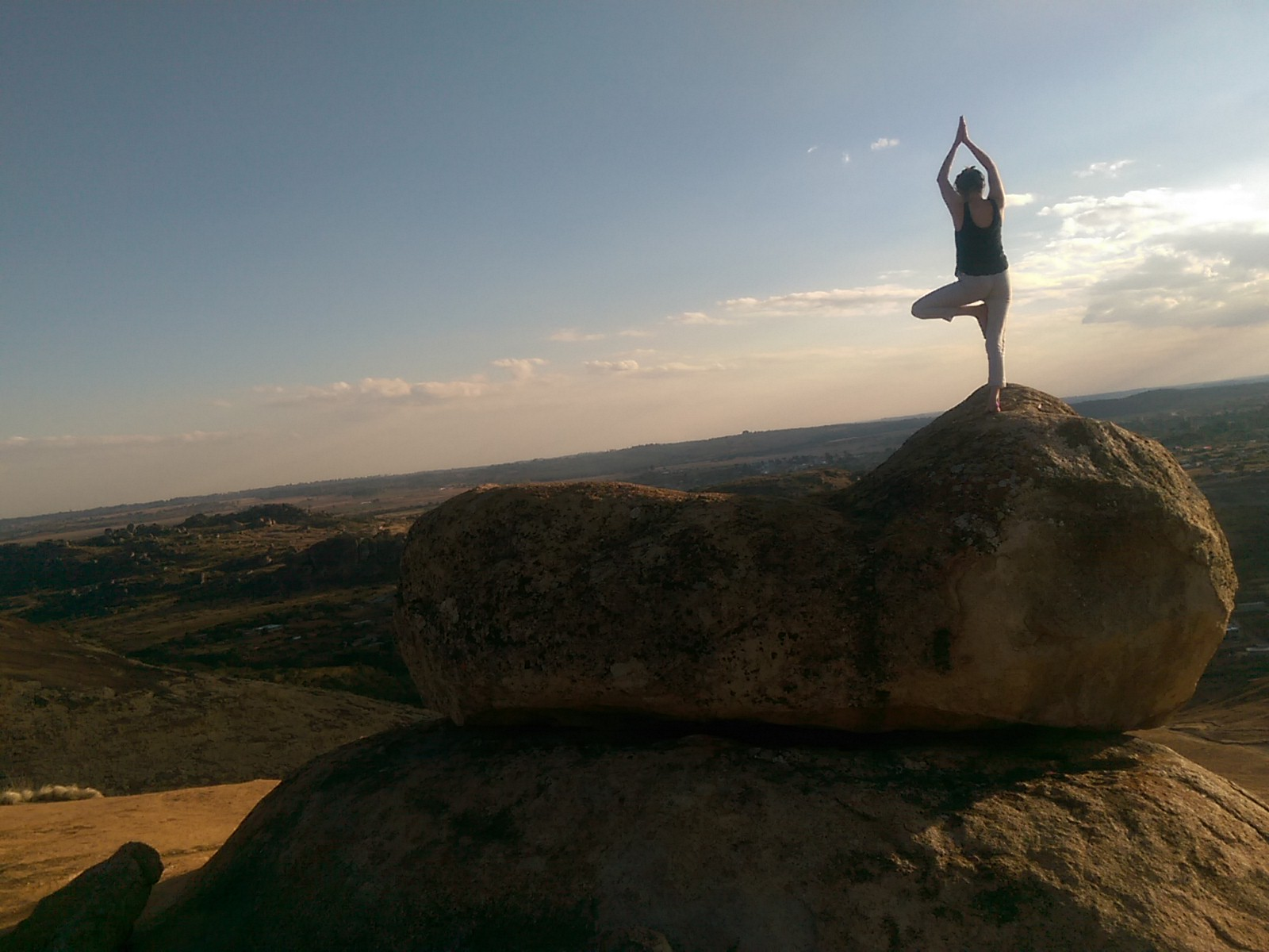 The silhouette of a woman doing yoga tree pose on a large rock with an epic view