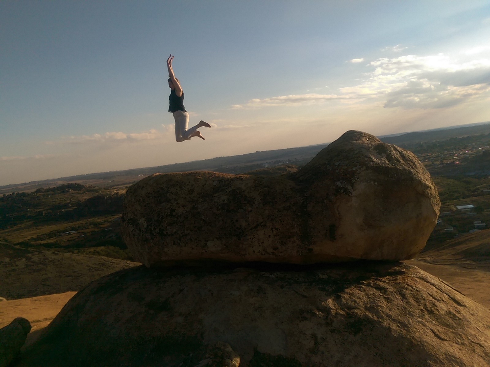The silhouette of a woman jumping with her arms above her head and legs behind her from a large rock with an epic view