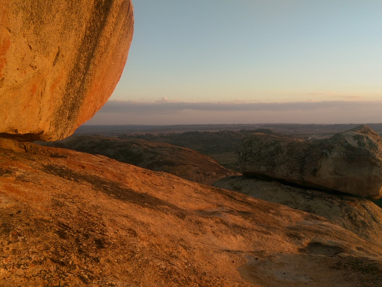 The edge of a large rock with a dusky sky and more rocks in the distance
