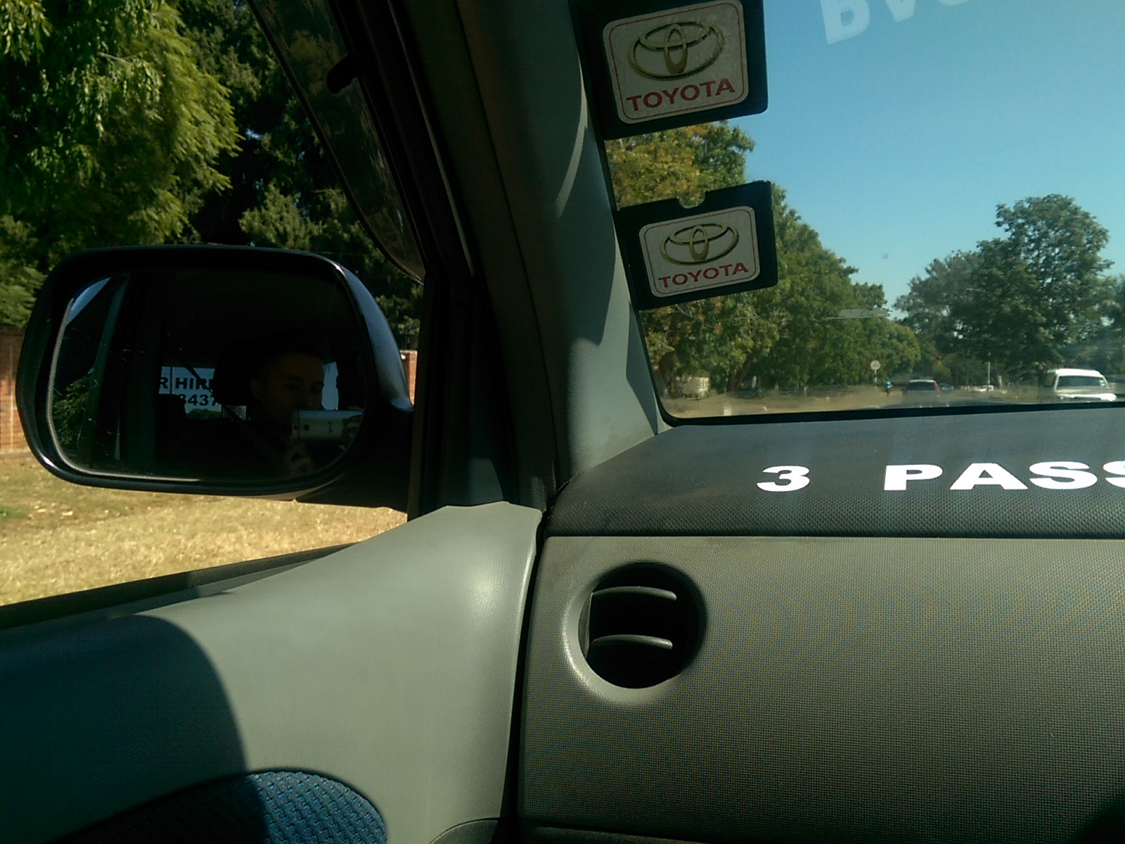 Perspective from inside the front seat of a car, with the wing mirror on the left and blue skies and trees