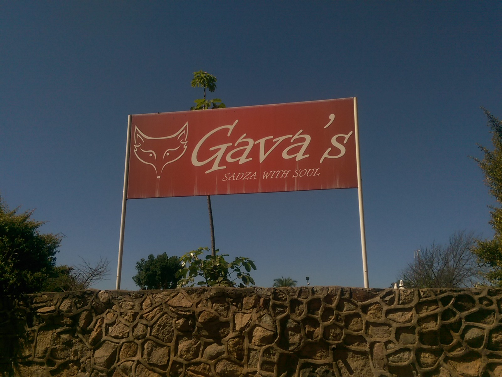 Red sign saying Gava's against a blue sky above a wall
