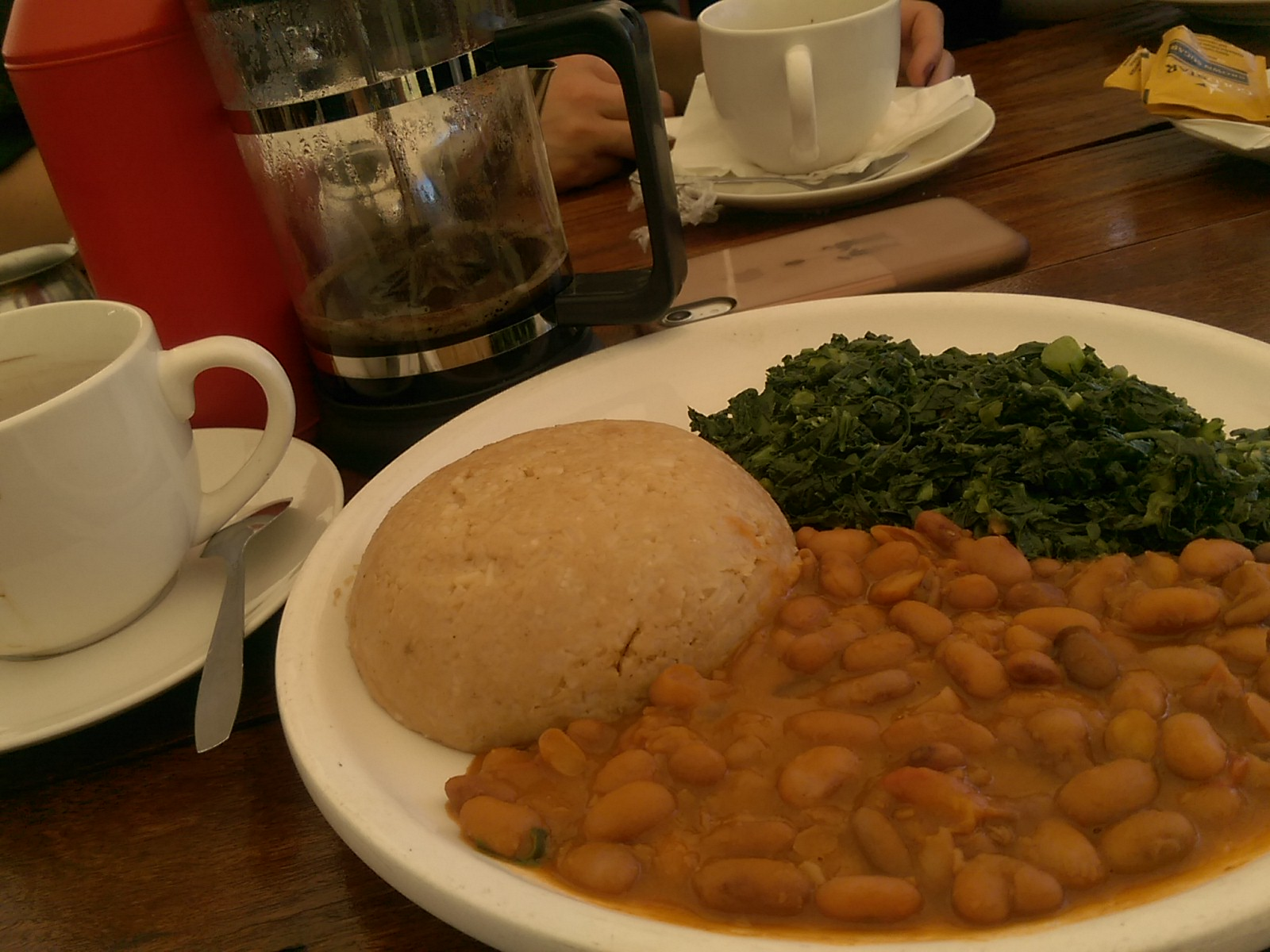 A plate with a round ball of rice beside beans and a pile of greens, French press in the background