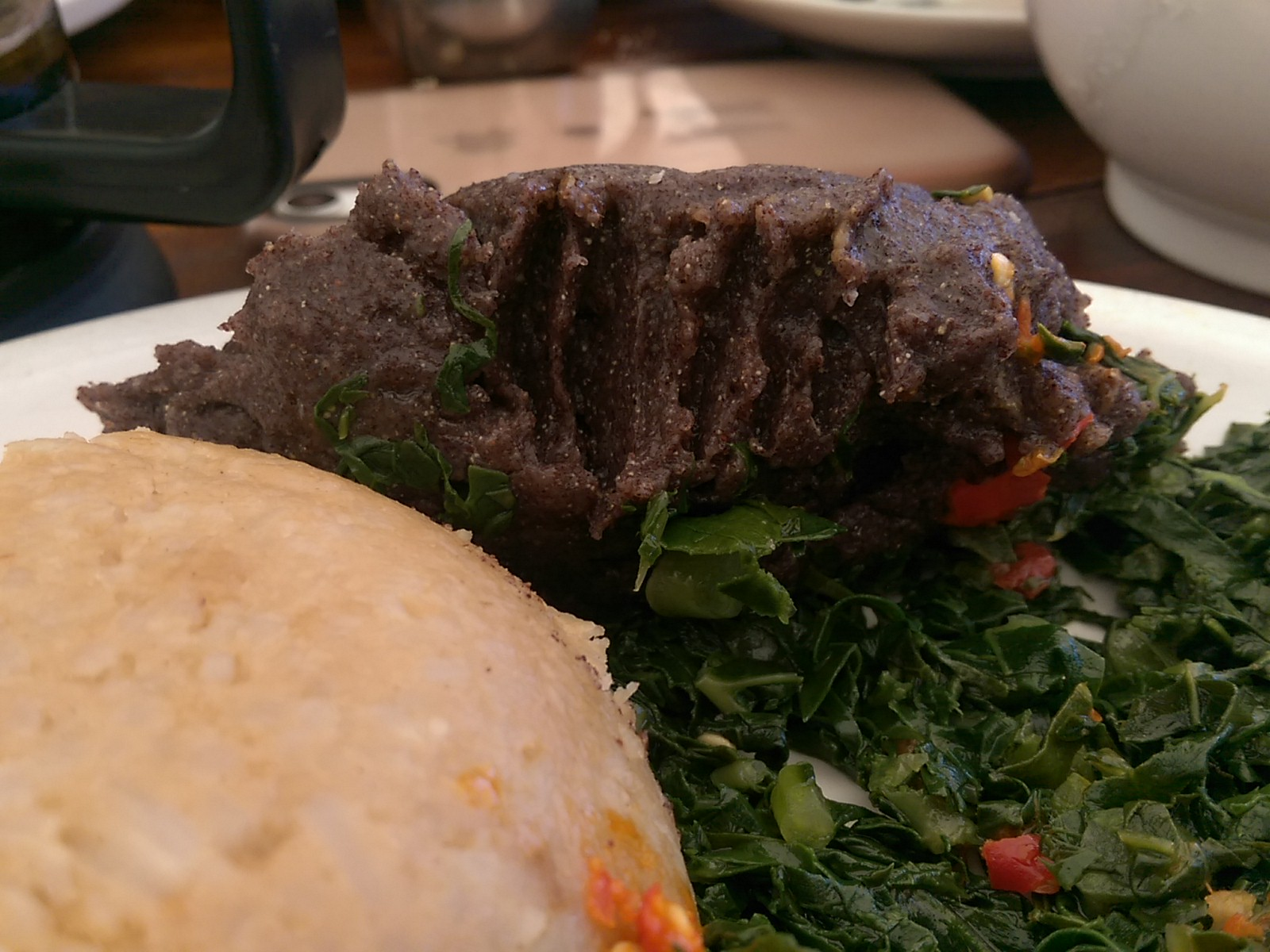 Close up of a black ball of sadza with forkmarks, sitting on some greens