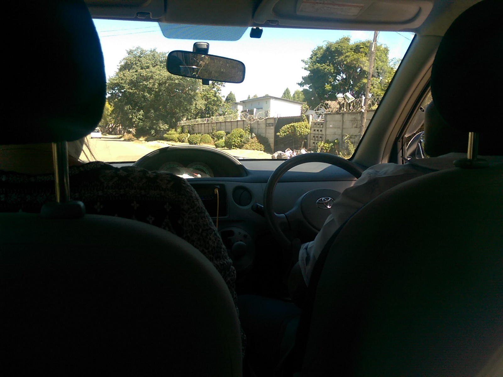 View from the back seat of a car to the front window and driver