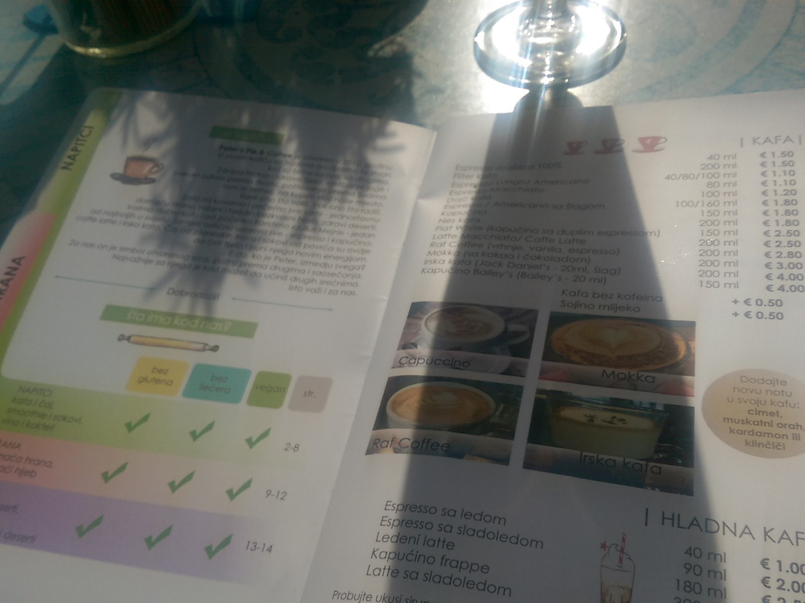 A menu open on the table with pictures of food and a key for dietary requirements, shadows from a glass and plant
