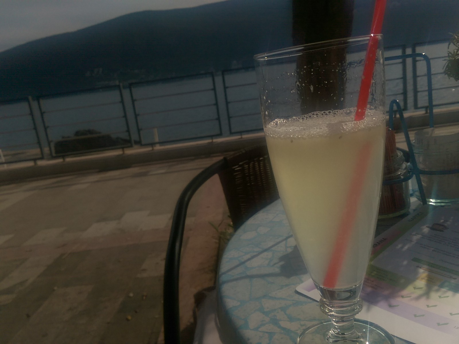 A glass of lemon juice on a table in the foreground with the sea and mountains in the background