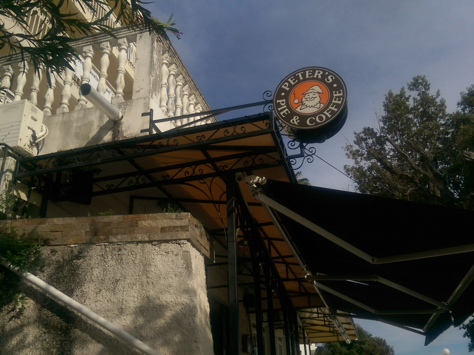 A cafe canopy from the side and below with a round orange sign