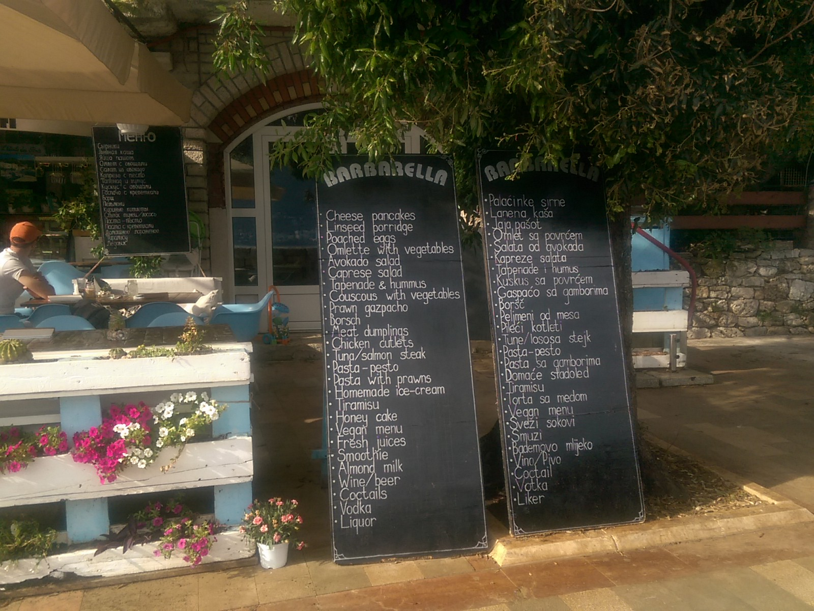 Two tall blackboards in front of a cafe with blue and white tables
