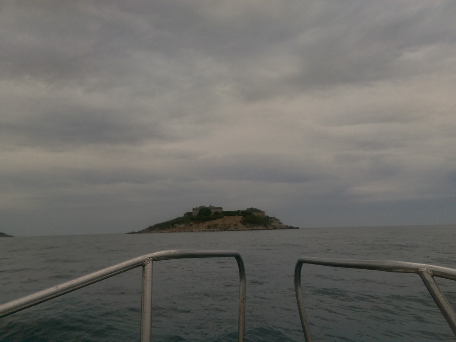 Handrails on the front of a boat in the foreground of moody grey sea with an island in the middle