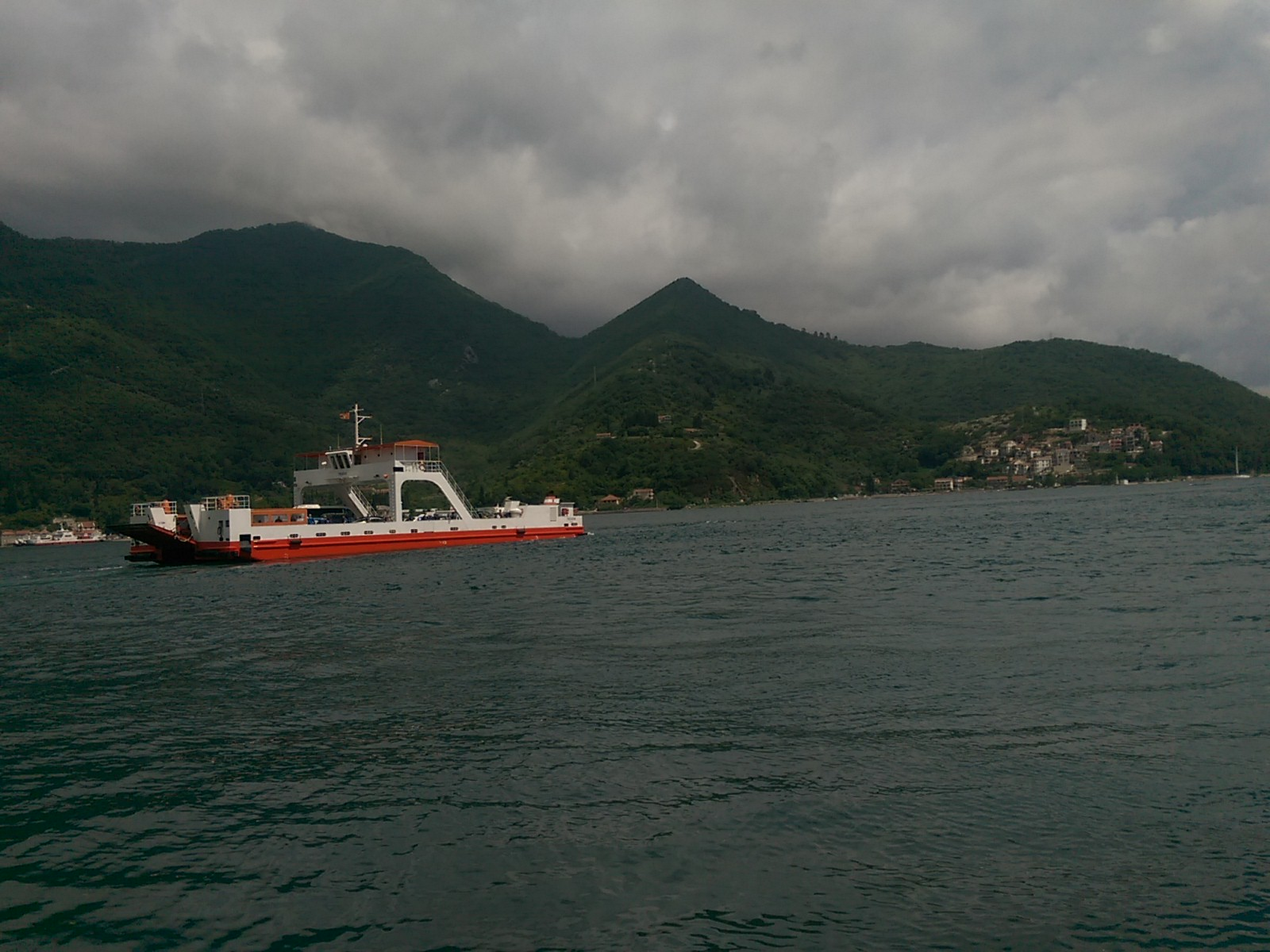 Moody cloudy skies over some pointy mountains by the sea, with a red and white car ferry crossing from left to right