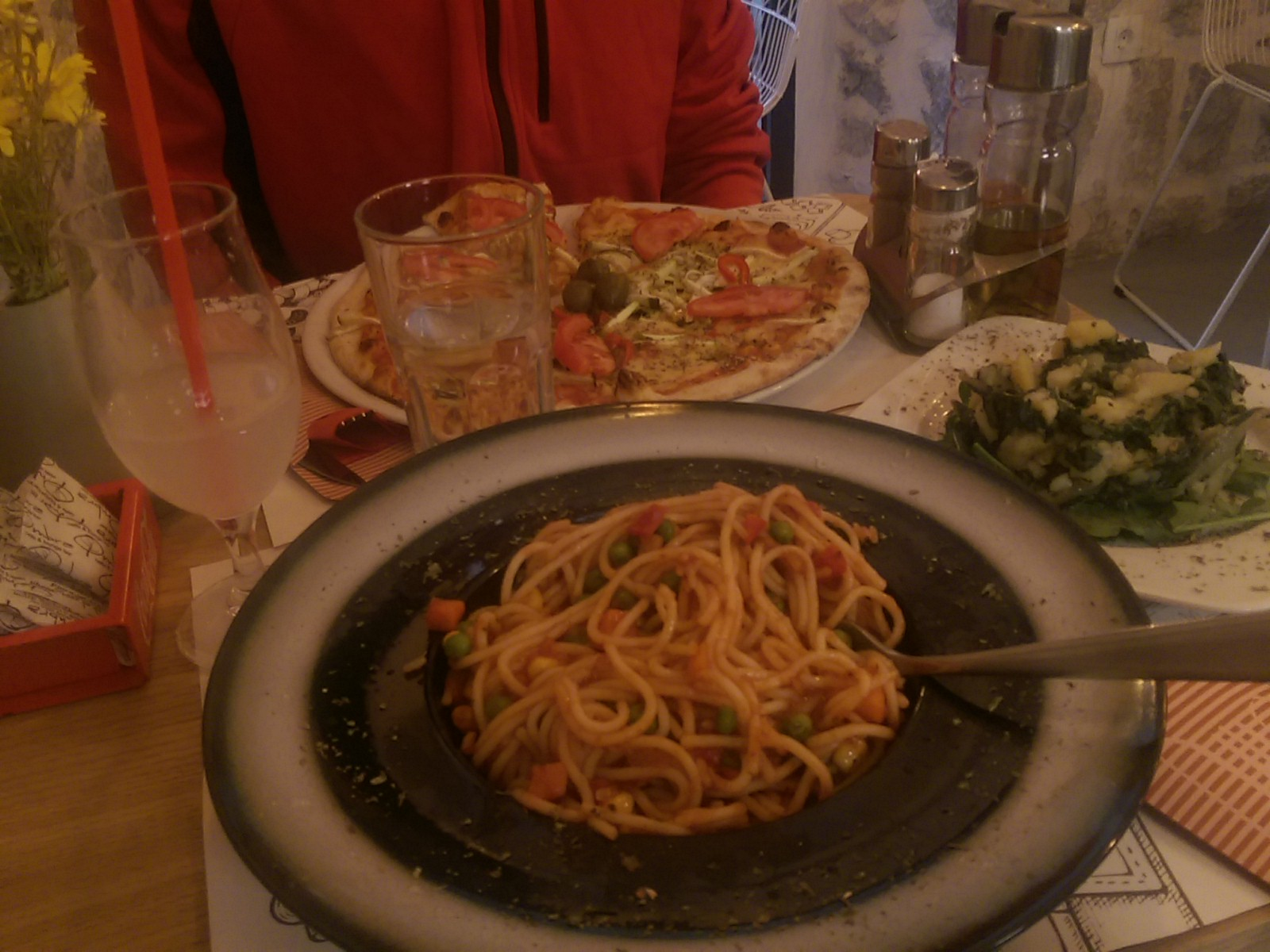 A table full of dishes, including spaghetti in the foreground, a wine glass with lemon juice, potatoes and chard on a plate, and at the far end a pizza