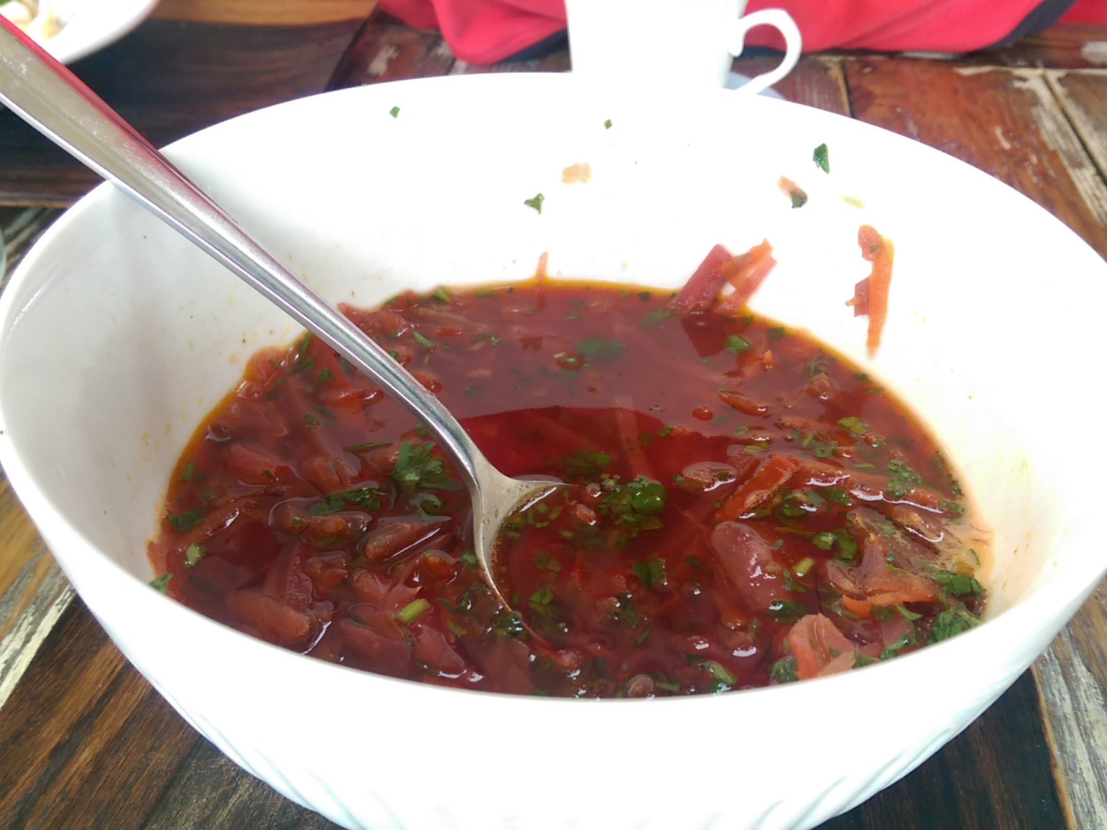 A white bowl of reddish pink soup with a spoon