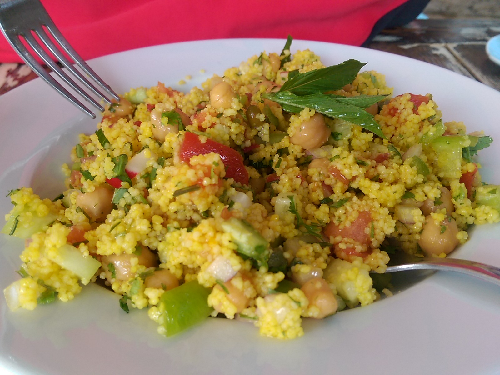 Bright yellow couscous and red and green peppers in a white bowl with a fork