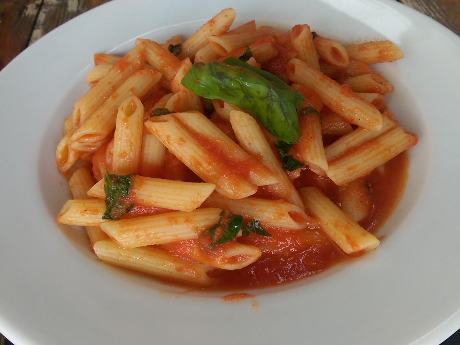 Penne pasta with tomato sauce and basil on top