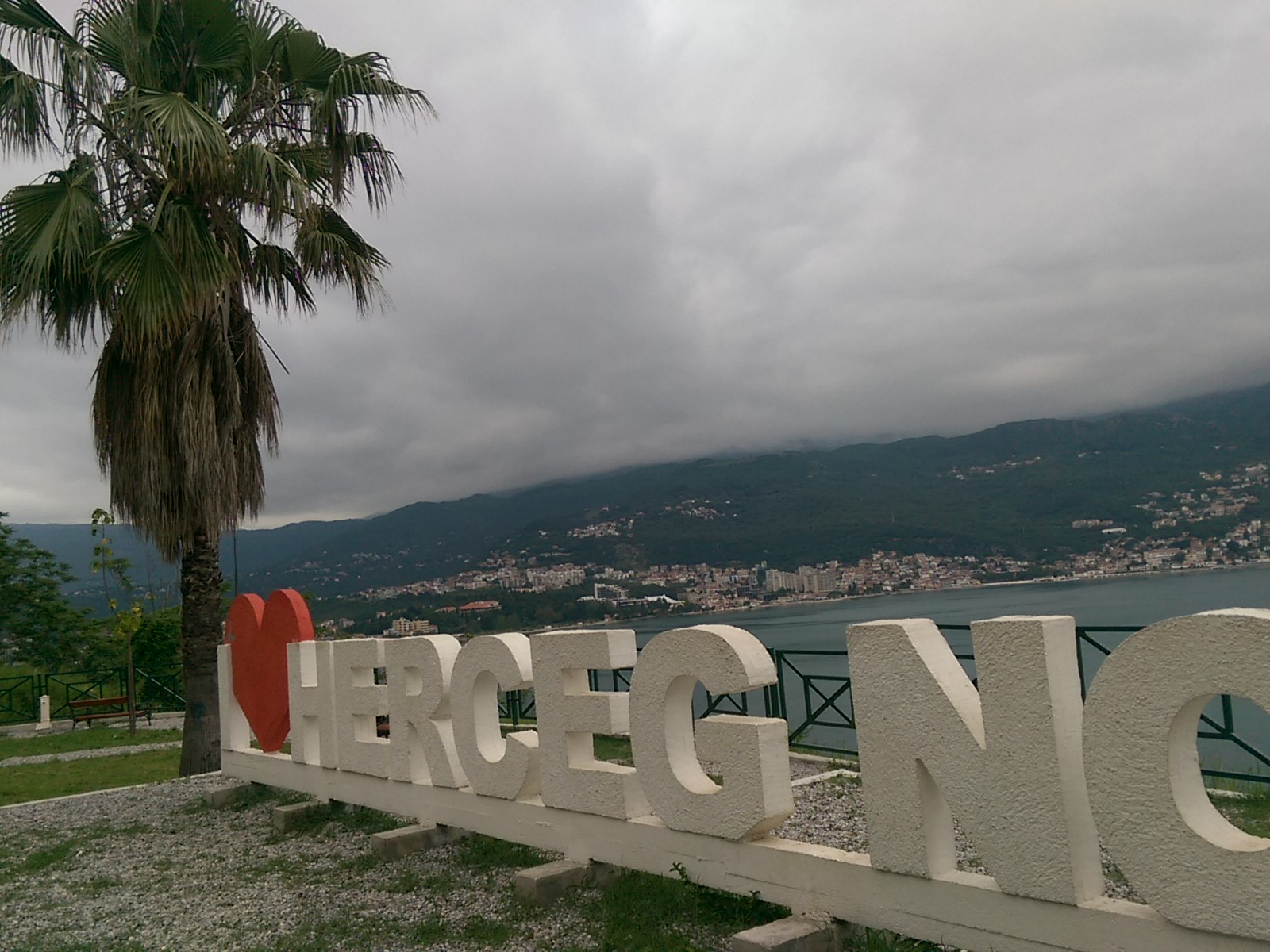 Giant I <3 Herceg Novi sign next to a palm tree in front of a distant bay view of a town, with thick white clouds over the mountains