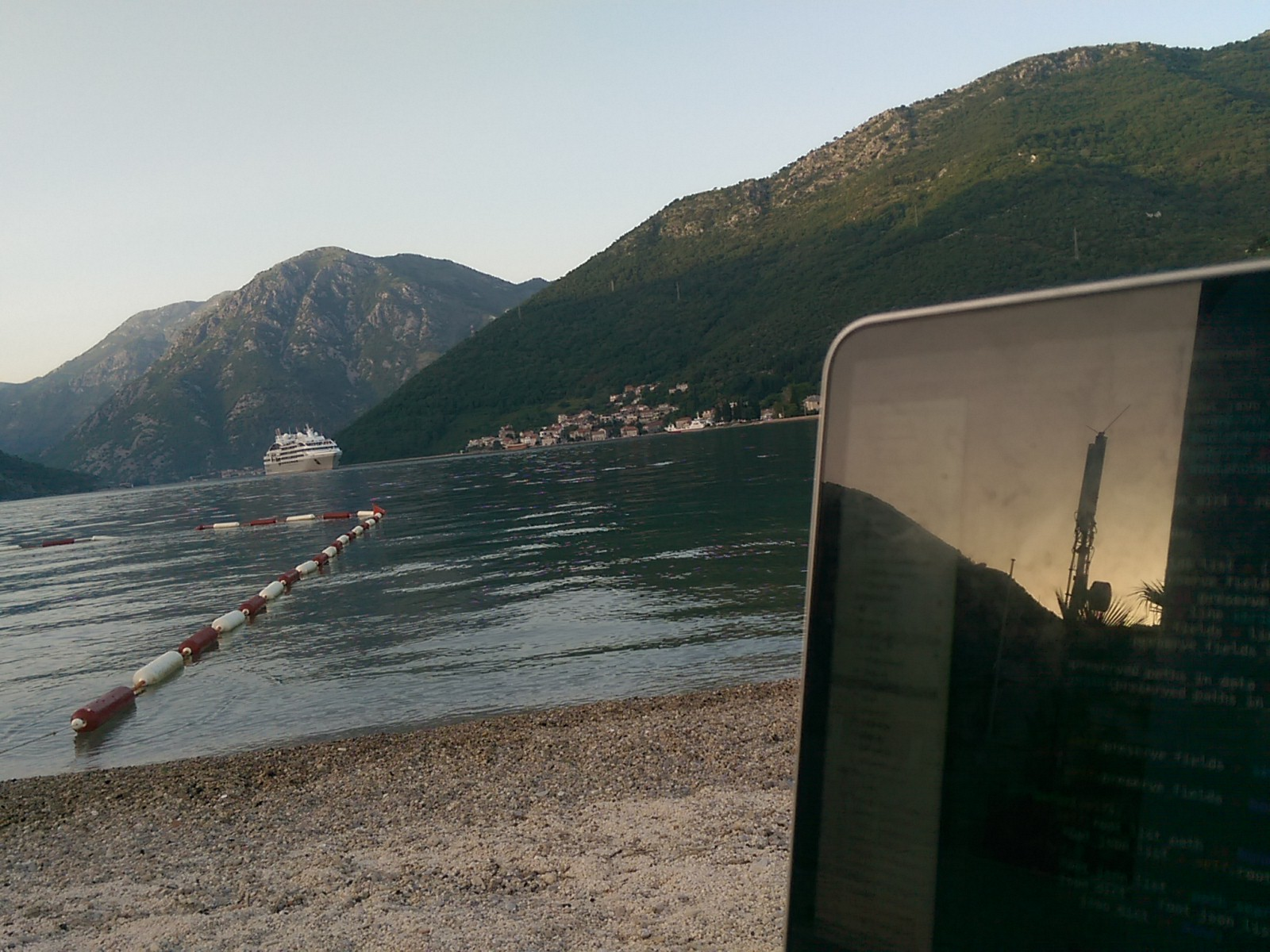 The corner of a laptop screen on the right side, with sand, sea, and green mountains behind