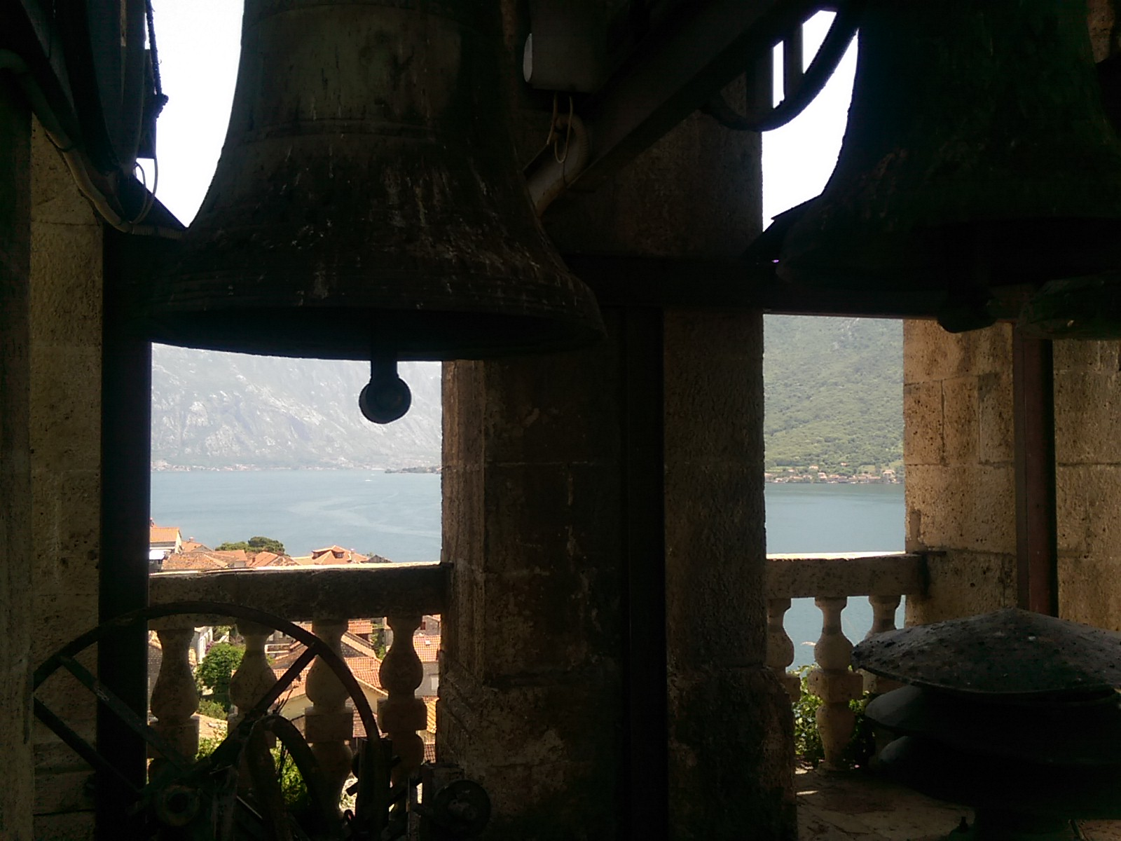 Old bells silhouetted against a backdrop of sea and mountains