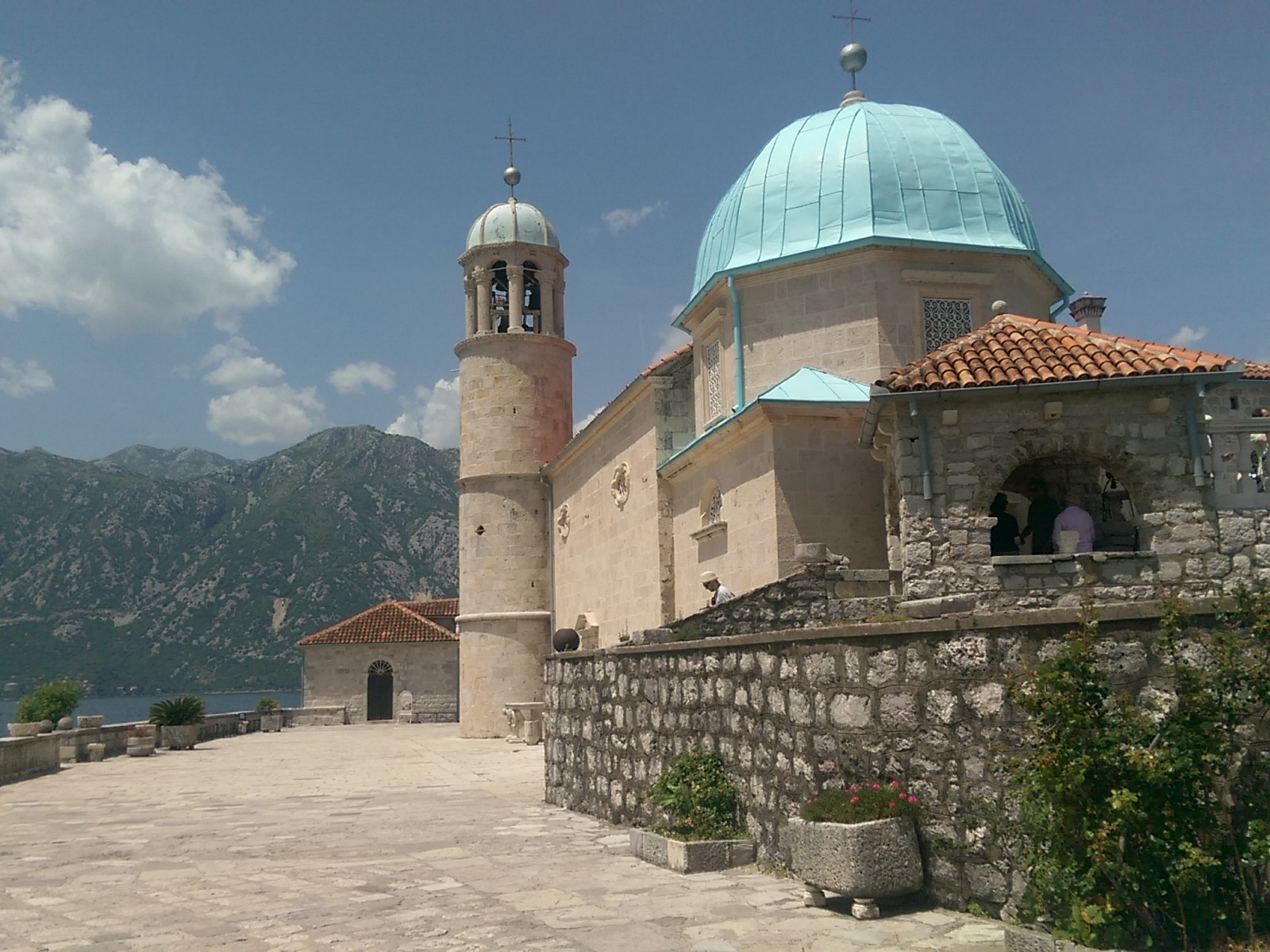 A stone church with a blue dome and a tower, with background mountains