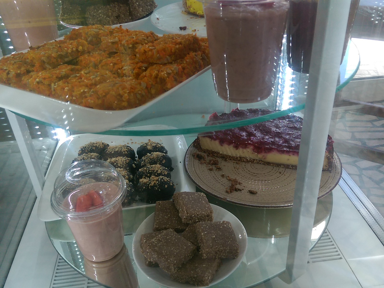 A glass counter with shelves of cakes