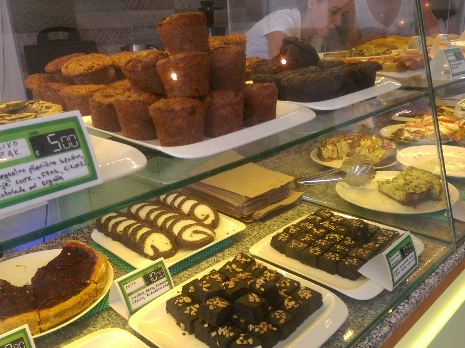A glass counter with muffins on top and chocoaltes and pie on the bottom