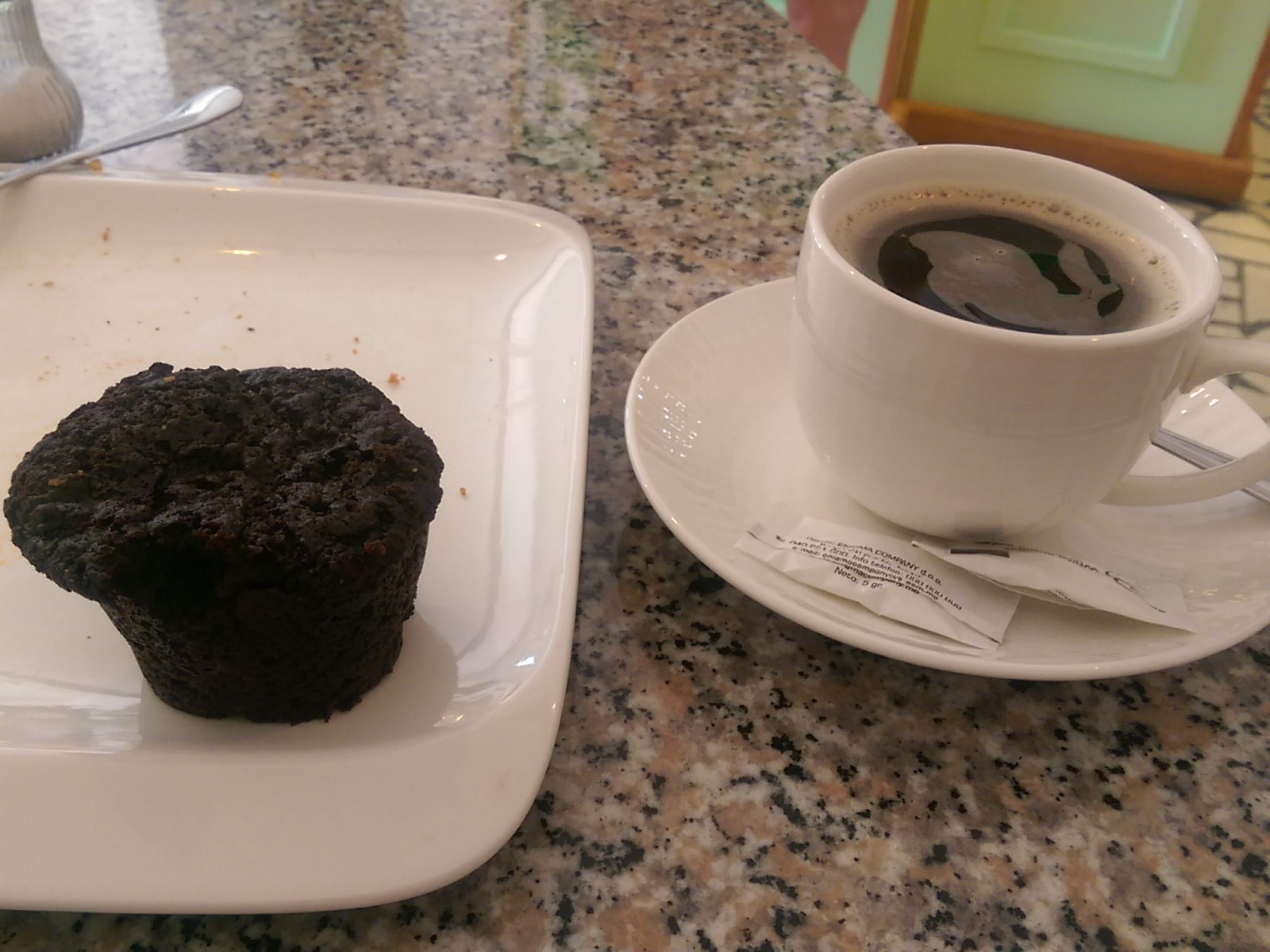 A chocolate muffin on a white plate beside a cup of something that looks like coffee but isn't