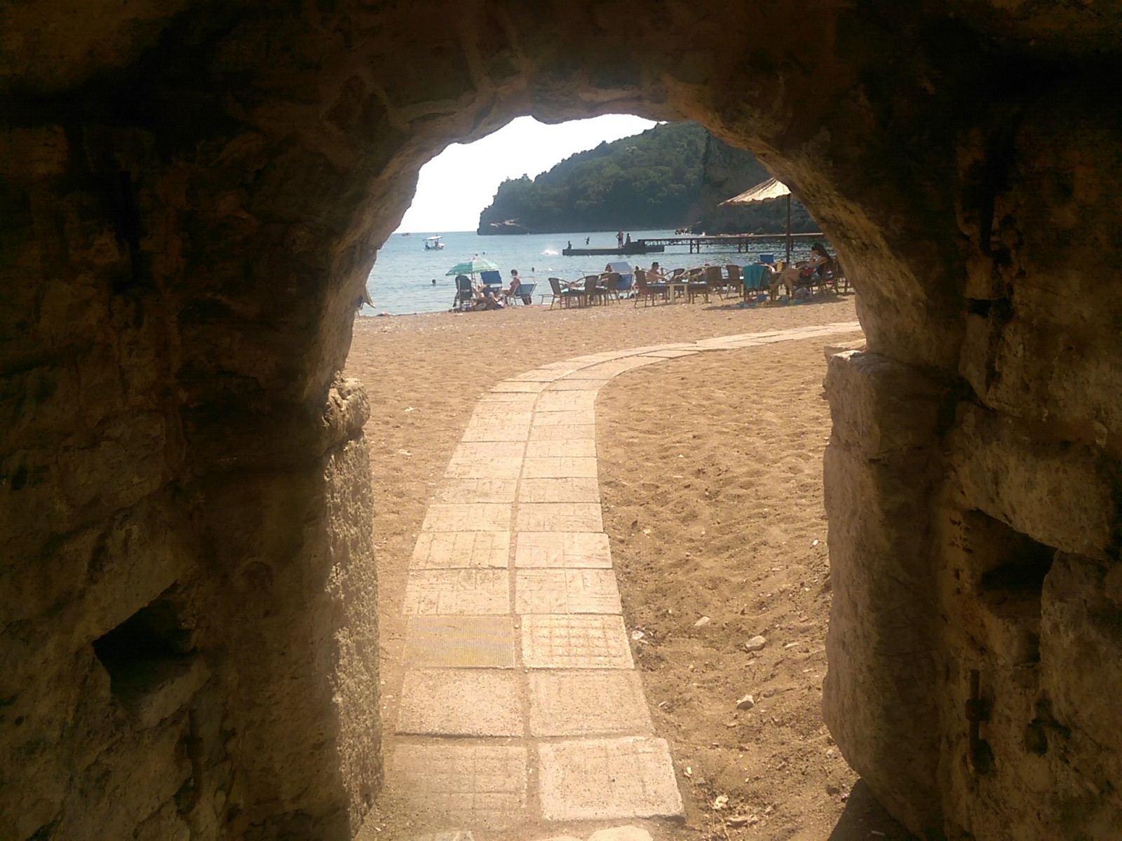 A stone archway opens directly to a beach with a tile path curving right through the sand, parallel with the sea
